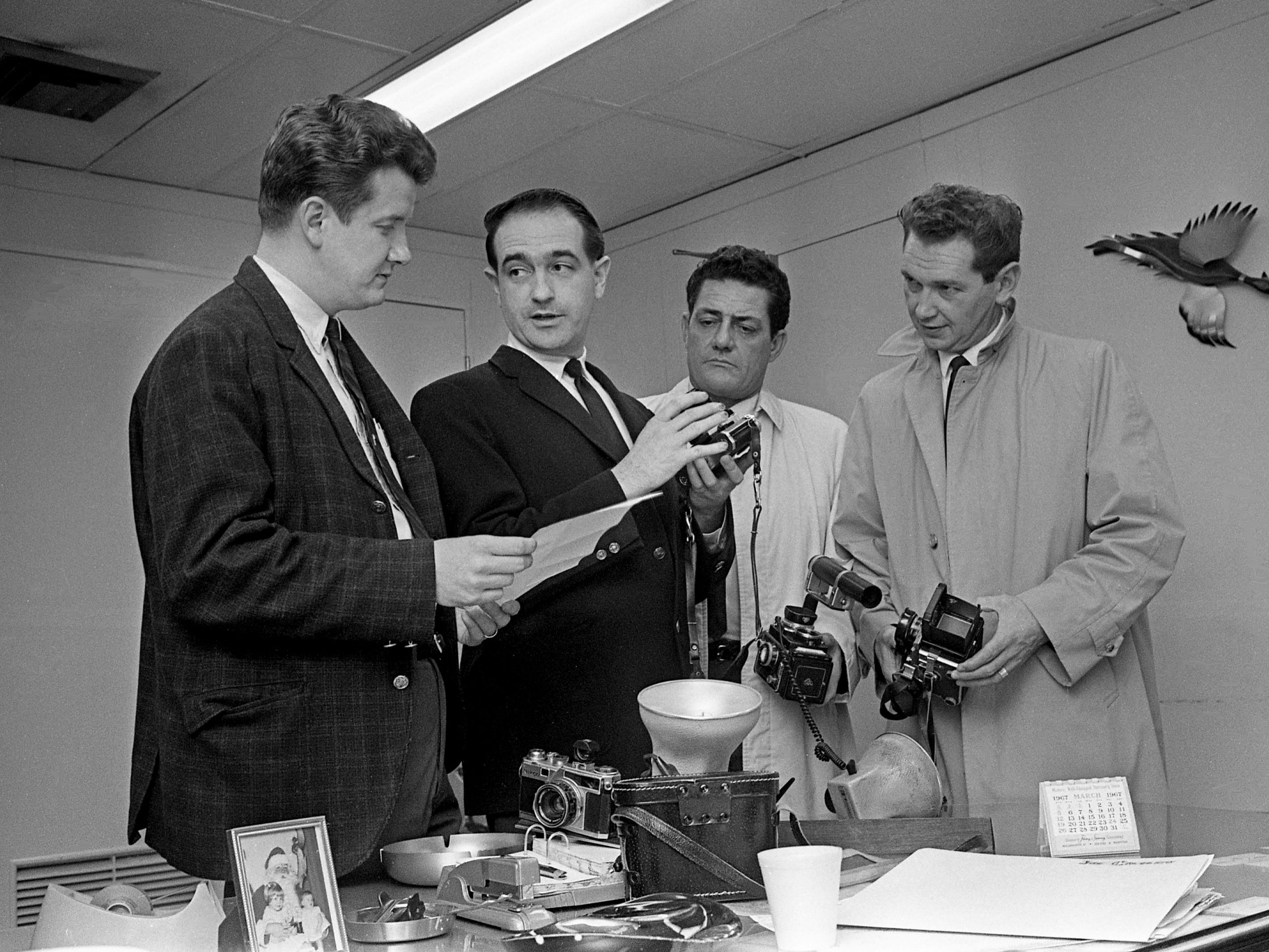 Detective Sgt. Doug Dennis, left, helps Tennessean staff photographer Frank Empson, second from left, identify cameras March 17, 1967, that were stolen Feb. 23. Detectives Archie Summers, right, and Guy Conquest aided in the recovery of the photographic equipment.