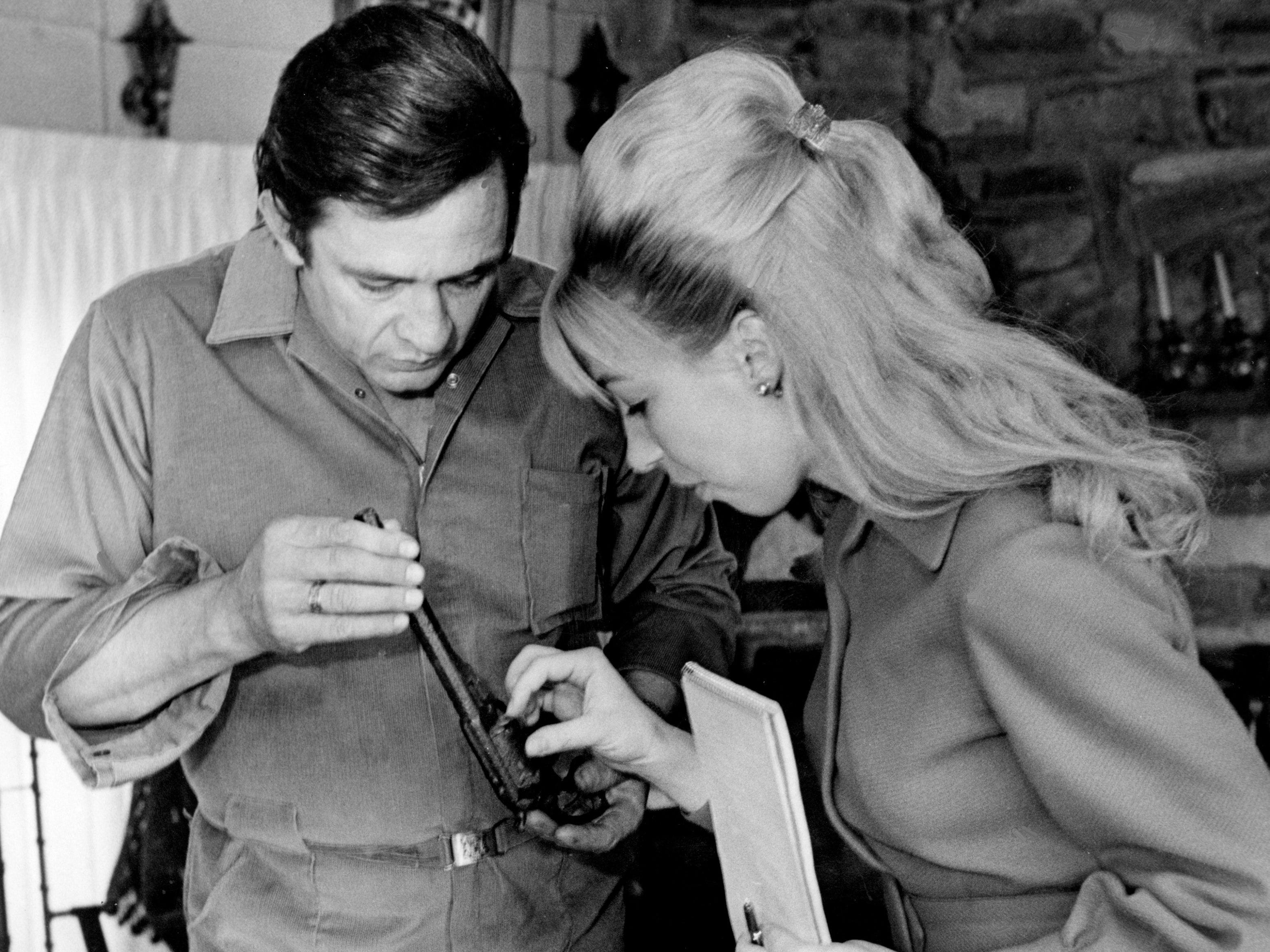 Johnny Cash shows off one of his antique pistols to Kathy Sawyer, a Tennessean reporter, April 19, 1969. Cash built a wagon-wheel showcase for his antique pistol collection, which includes mostly Colts and a couple of French dueling pistols.