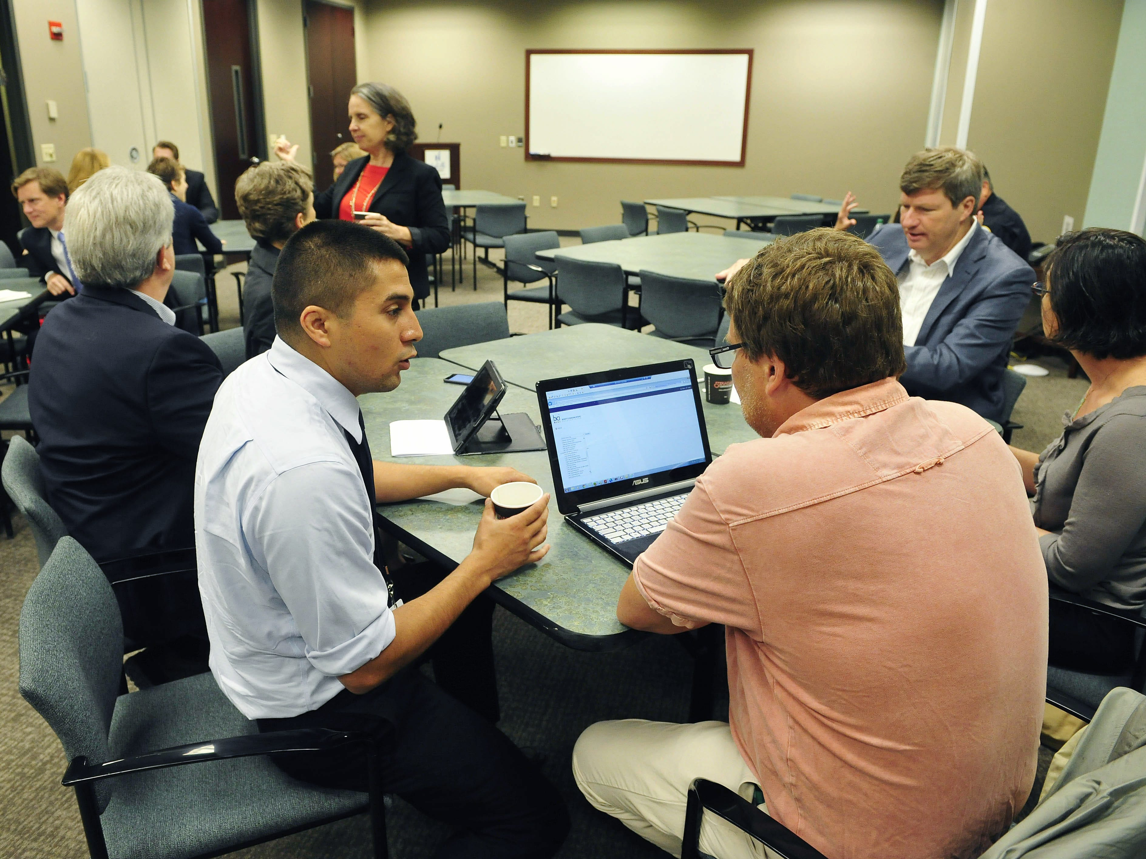 Tennessean reporter Jason Gonzales, front left, talks with TC Weber during a Project RESET meeting hosted by The Tennessean at the Nashville Chamber in downtown Nashville on May 21, 2015.
