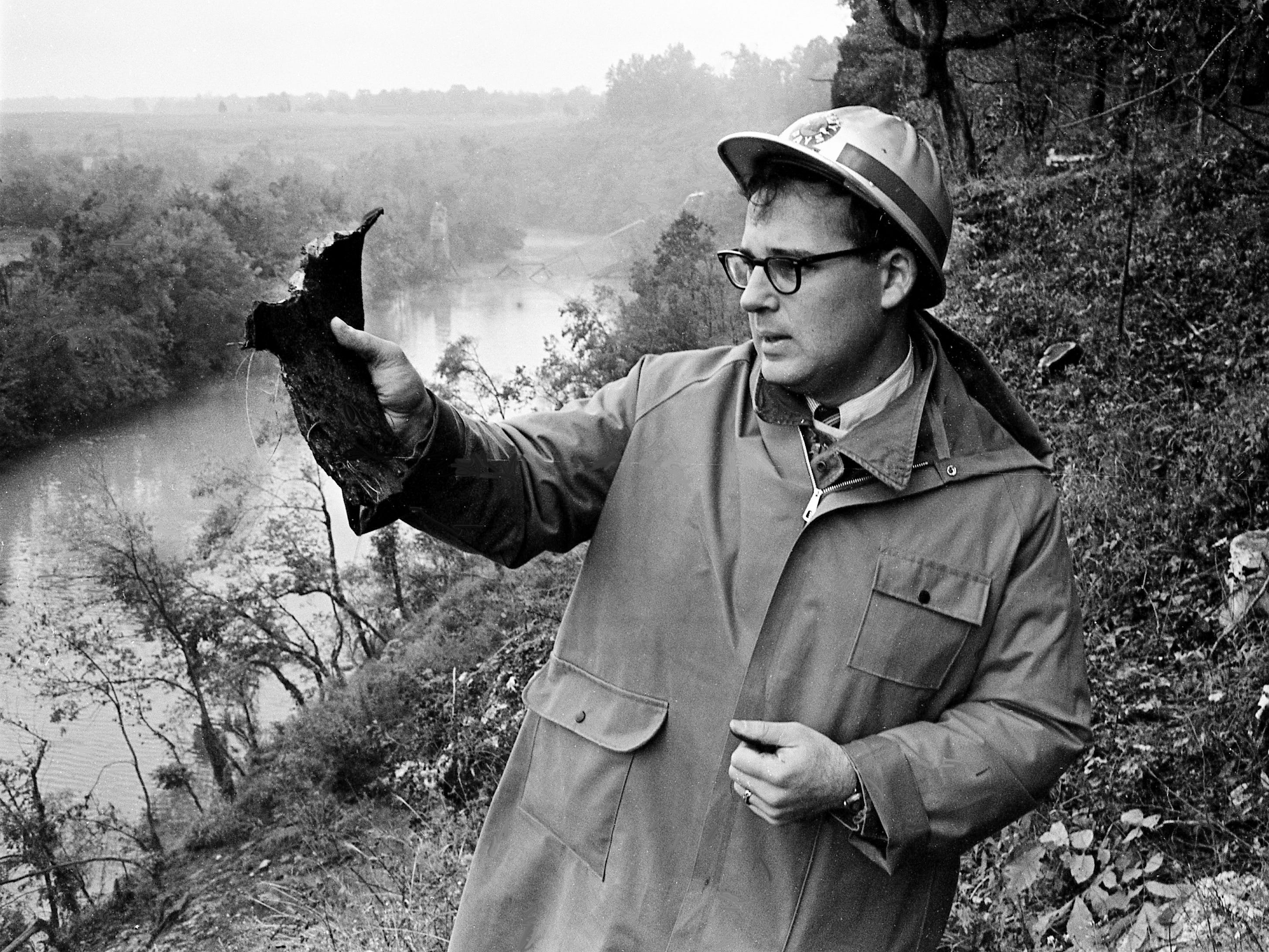 Tennessean reporter William Greenburg stands on a bluff over the Stones River examining a piece of shrapnel that hurtled 1,300 feet over the trees by the Couchville Pike bridge blast Sept. 28, 1967, and landed close to observers.