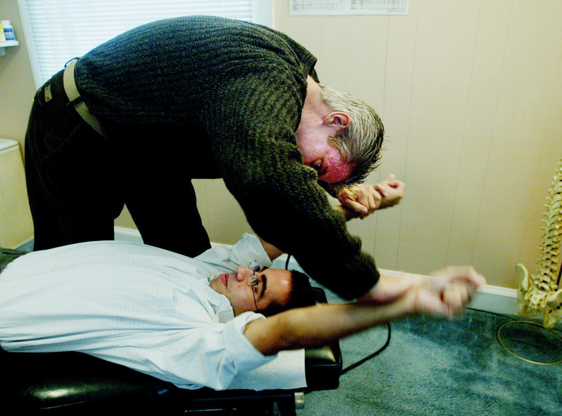 Tennessean reporter Sameh Fahmy, bottom, has an applied kinesiology muscle test to check his lymphatic system by Dr. Brent Davis, a chiropractor, for a story Oct. 14, 2004.
