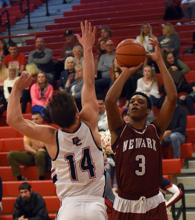 Grove City junior Cole Crager tries to block a shot from Newark's Keshawn Heard during Tuesday night's game at Grove City. The Wildcats won 61-47 on the road.