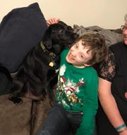 Caleb loved dogs, and they loved him back. In this recent photo, a black Lab shows its affection for the boy at a New Year's Eve party at a home in Beachwood.