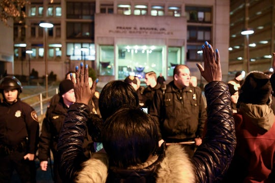 Protesters hold their hands up in front of Paterson police officers during a rally calling for justice for Jameek Lowery on Tuesday, Jan. 8, 2019, in Paterson. Lowery died two days after going on Facebook Live claiming that someone was out to kill him and asking the Paterson Police Department for help.