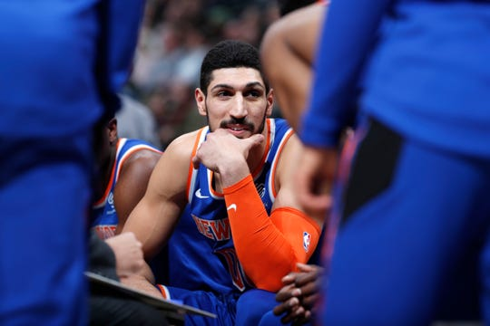 New York Knicks center Enes Kanter jokes with teammates during a timeout the first half of the team's NBA basketball game against the Denver Nuggets on Tuesday, Jan. 1, 2019, in Denver.