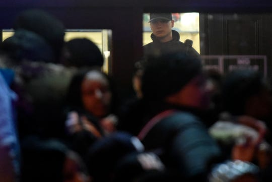 A police officer watches the crowd from inside Paterson City Hall as activists call for justice for Jameek Lowery on Tuesday, Jan. 8, 2019, in Paterson. Lowery died two days after going on Facebook Live claiming that someone was out to kill him and asking the Paterson Police Department for help.