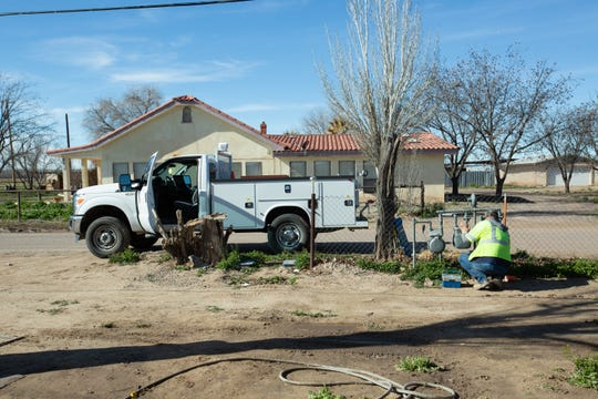 A New Mexico Gas Company worker stops and tends to the meters at a home near the site of a Kinder Morgan pipeline that burst Dec. 13, 2018 northwest of Anthony, New Mexico and southwest of Berino. The pipeline break has since been repaired, but Kinder Morgan is carrying out site cleanup.