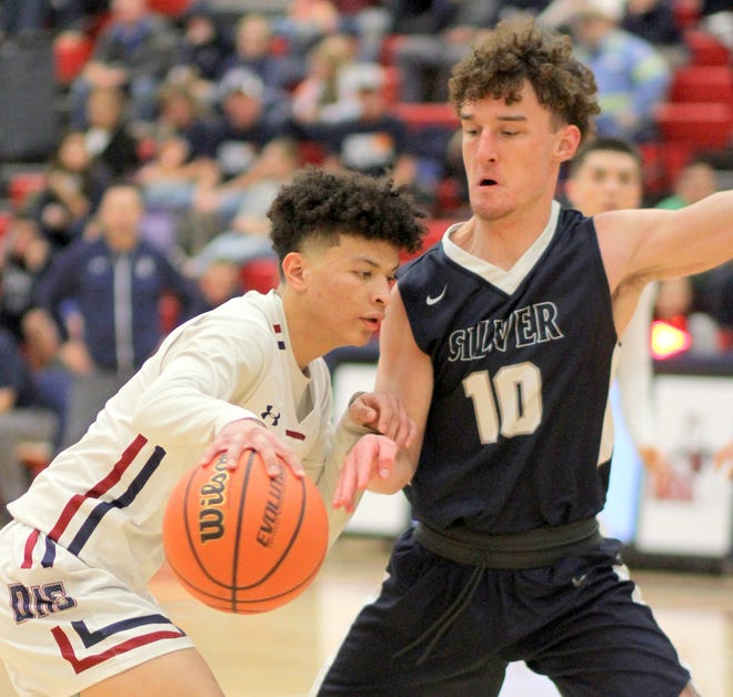 Senior Tristan Moore applies pressure on Deming guard Nathan Arroyos during Silver's 58-48 victory at Deming High School. The Fighting Colts improved to 10-2 on the season and earned a sweep of the home-and-away series with the Wildcats.
