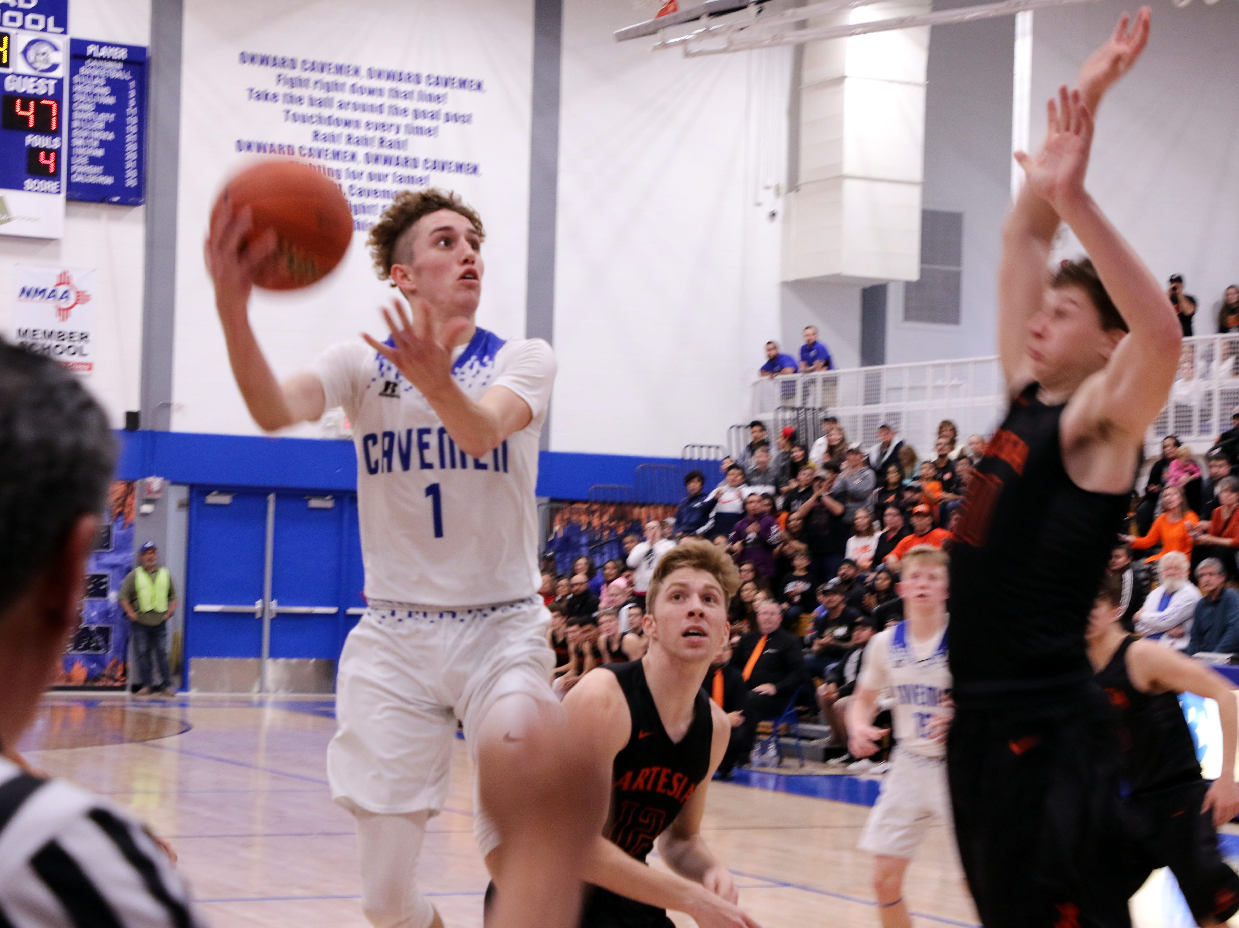 Carlsbad's Josh Sillas goes for a layup while Artesia's Clay Houghtaling goes for a block during Tuesday's game.