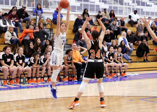 Carlsbad's Morgan Boatwright (21) passes to a teammate while Artesia's Paityn Houghtaling (34) tries to deflect the ball.