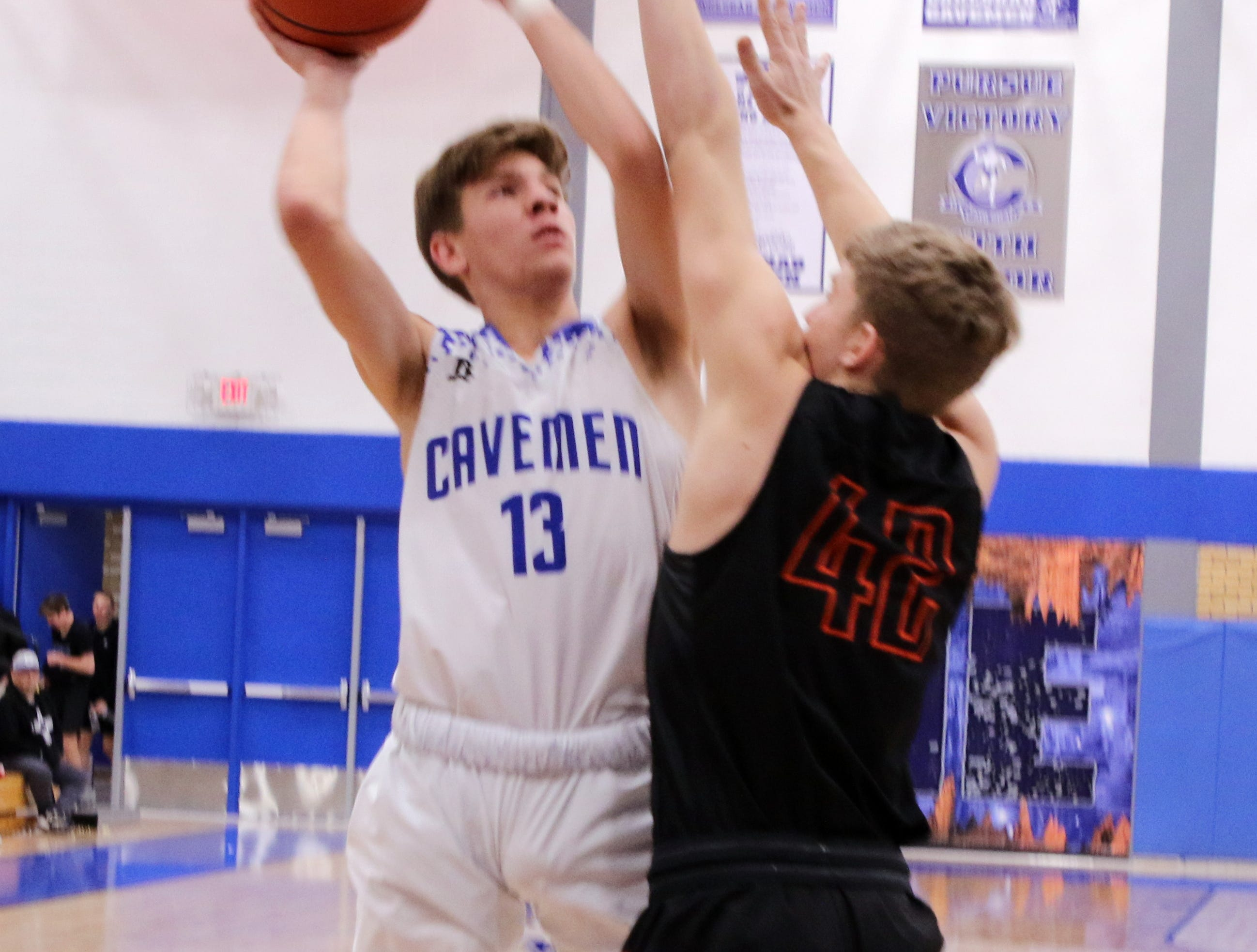 Carlsbad's Stevie Bartlett (13) goes for a contested layup against Jacob Creighton (42) during Tuesday's game. Carlsbad beat Artesia, 71-58.