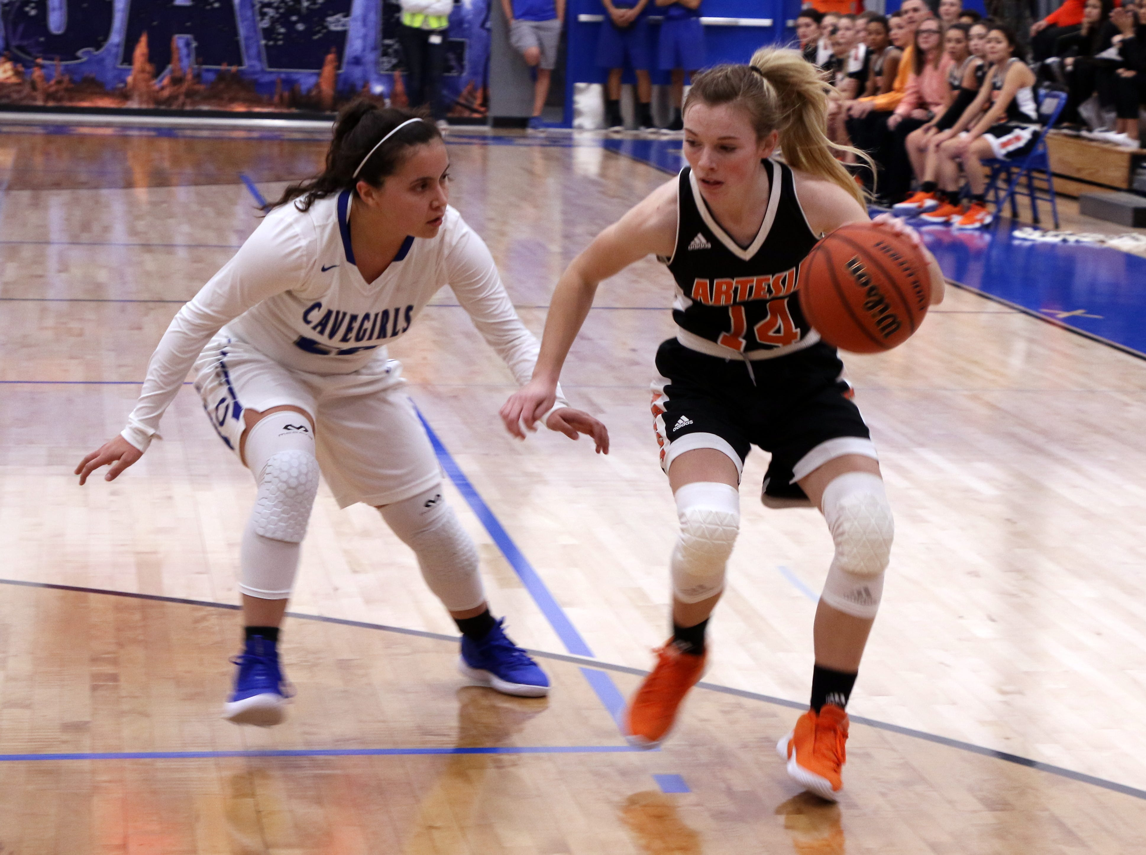 Artesia's Brehnan Davis (14) drives against Carlsbad's Nyah Chacon (22) during Tuesday's game.