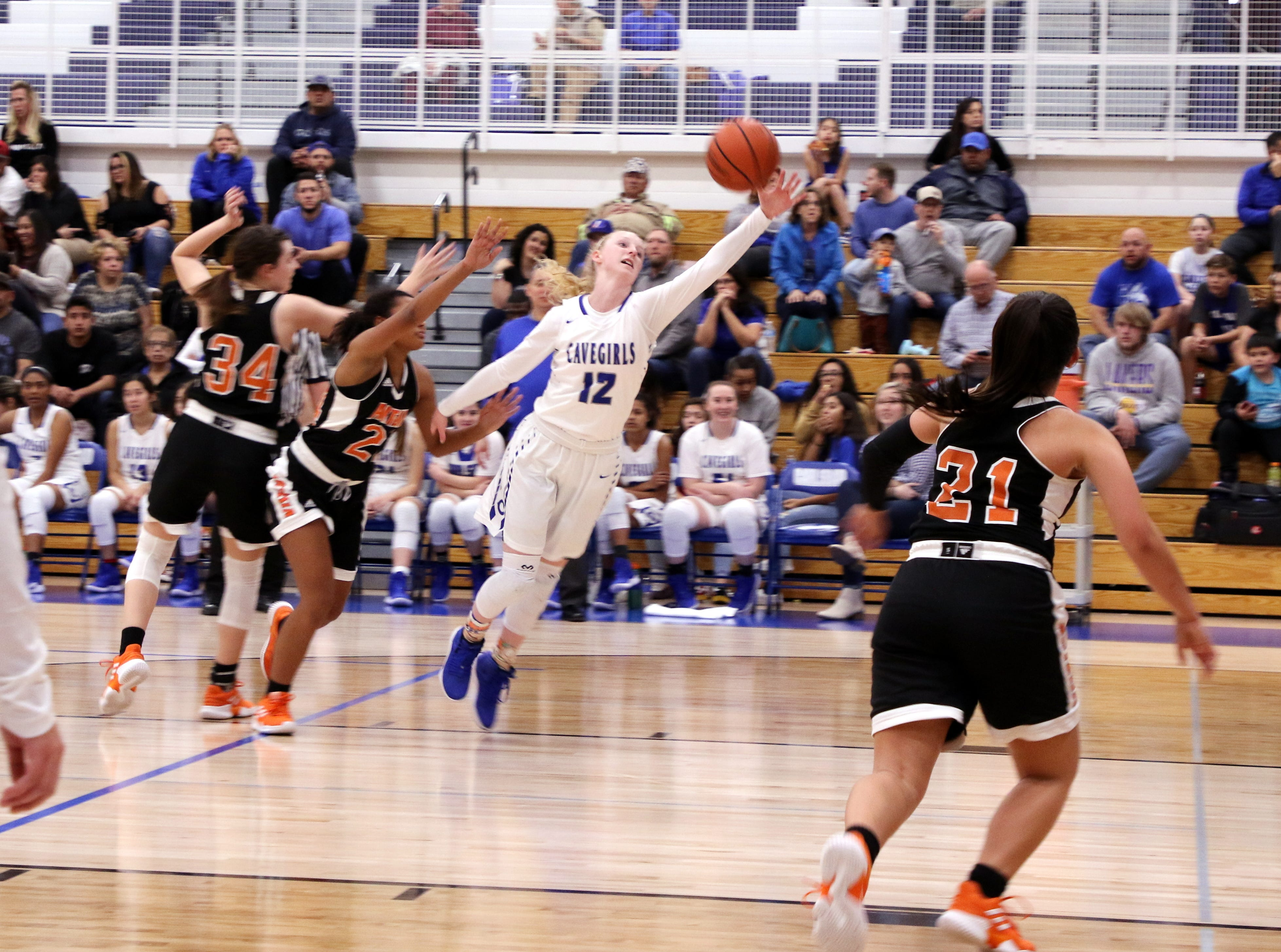Carlsbad's Carsyn Boswell (12) catches a lob pass in the paint during Tuesday's game against Artesia. Boswell finished with 18 points.