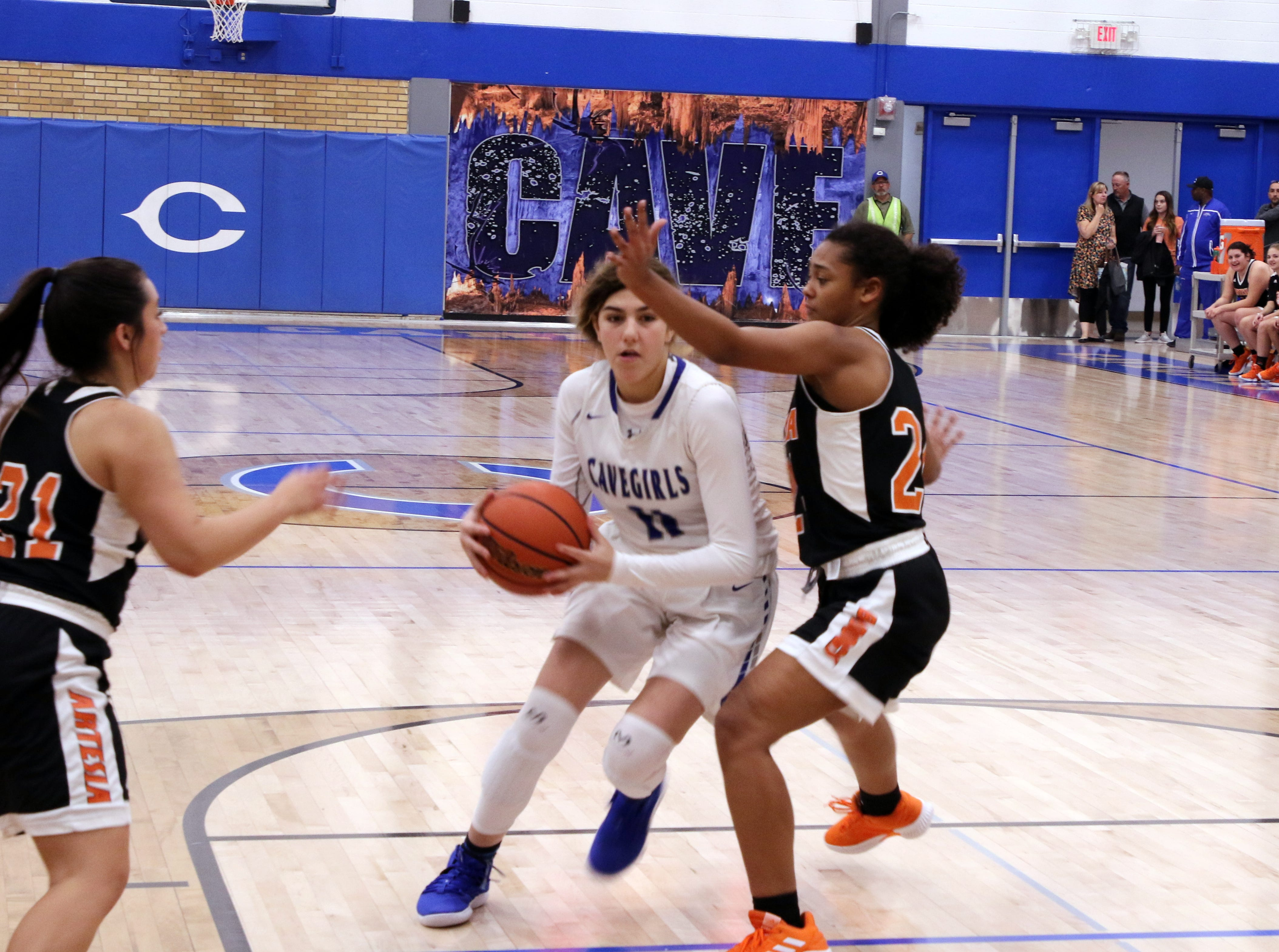 Carlsbad's Teran Tiller (11) drives through Artesia's Kyrah Gonzales (21) and Elliot Harrison (24) during Tuesday's game. Carlsbad beat Artesia, 61-32.