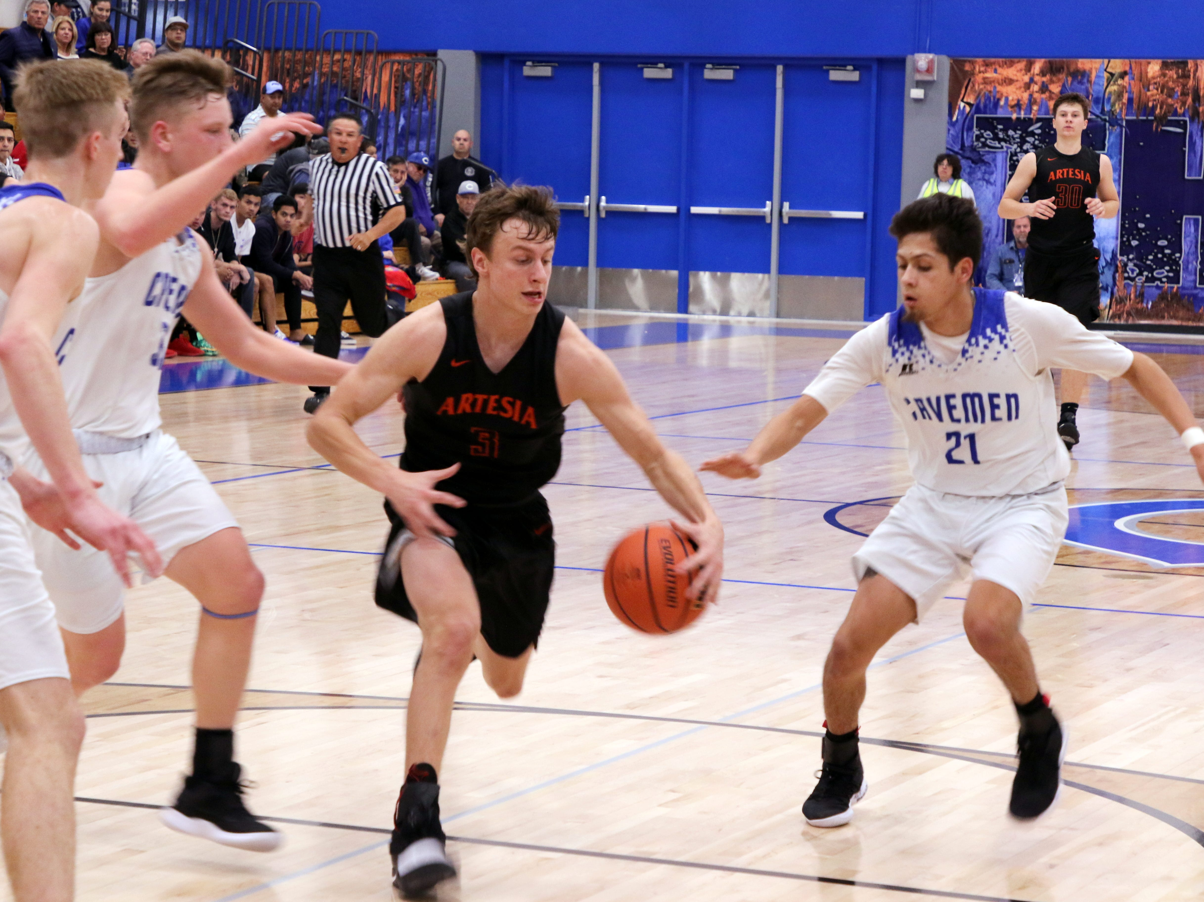 Cody Smith (3) dribbles between three Carlsbad defenders during Tuesday's game.