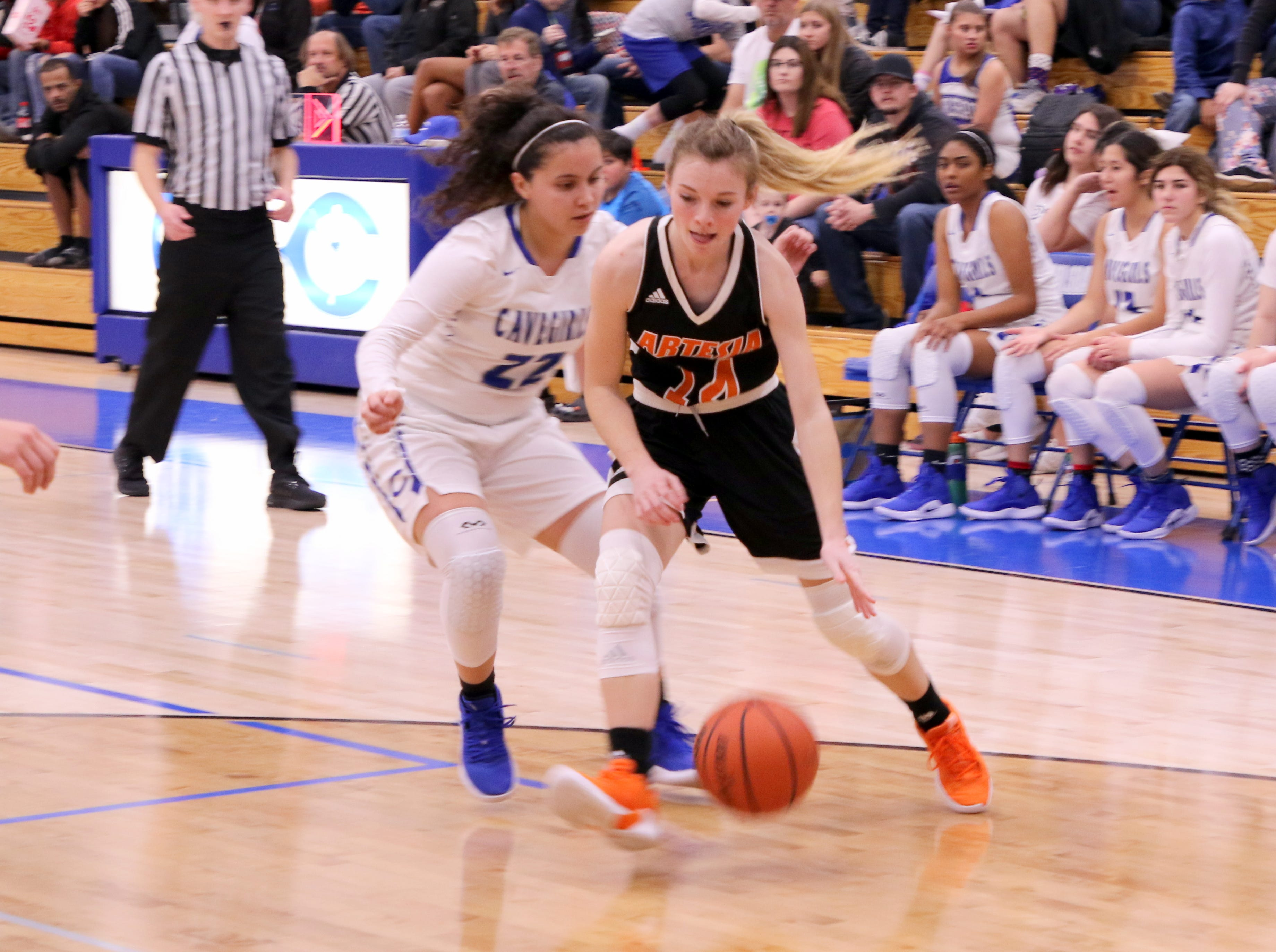 Artesia's Brehnan Davis (14) drives against Carlsbad's Nyah Chacon (22) during Tuesday's game. Davis finished with eight points.