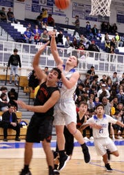 Ayden Parent (33) and Anthony Armendariz (32) battle for a rebound during Tuesday's game. Carlsbad beat Artesia, 71-58.