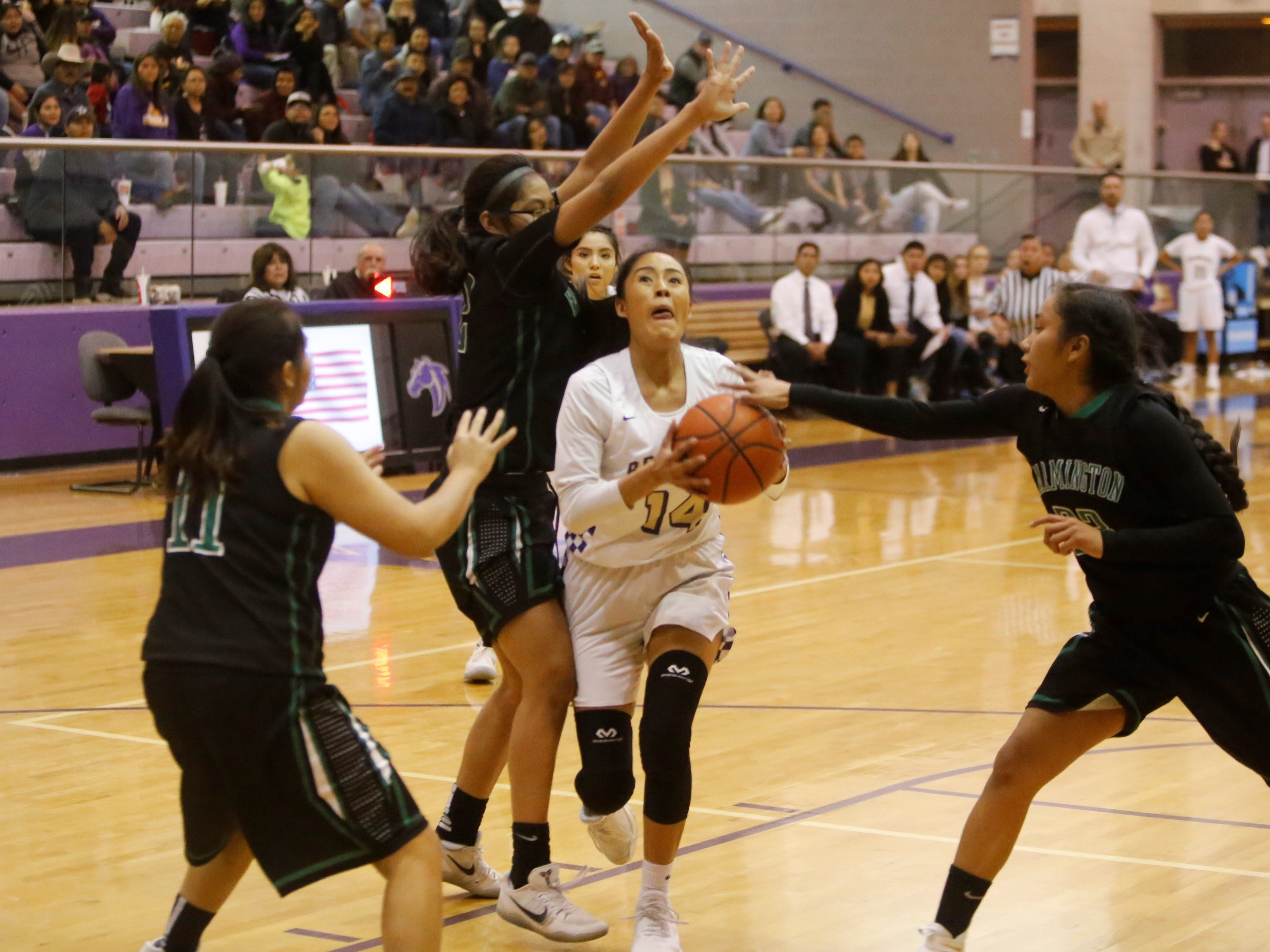 Kirtland Central's Shayonna Begay attacks the basket against Farmington's Philinda Nez (11), Germaine Steven (12) and Kiiyani Anitielu (23) during Tuesday's game at Bronco Arena in Kirtland.