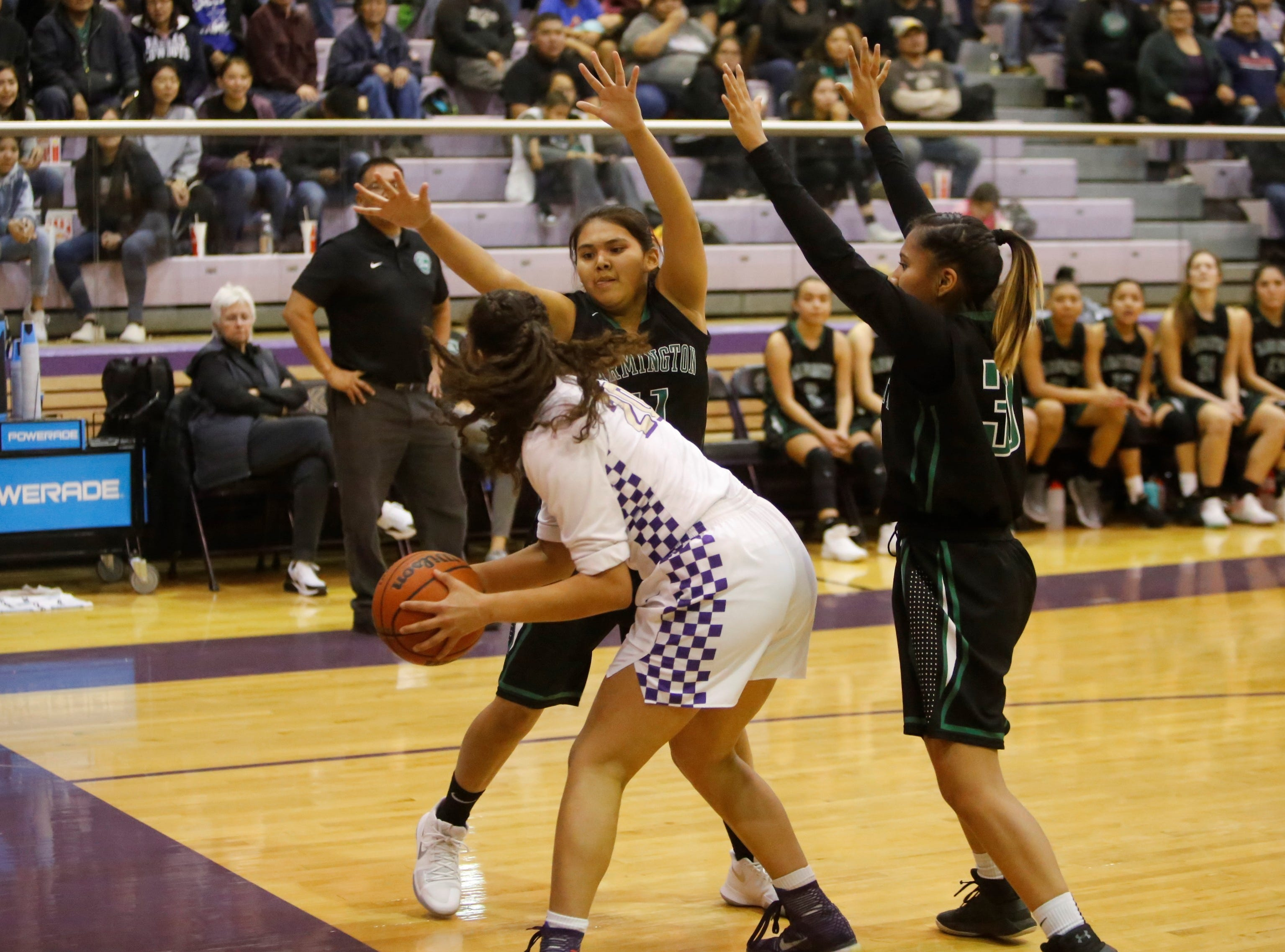 Farmington's Philinda Nez (11) and Carolyn Thomas (30) swarm around Kirtland Central's Siigrid Lii'bilnaghahi during Tuesday's game at Bronco Arena in Kirtland.