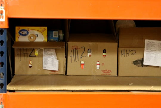 Food boxes for families with two members are stored on a shelf Wednesday at the ECHO Food Bank in Farmington.