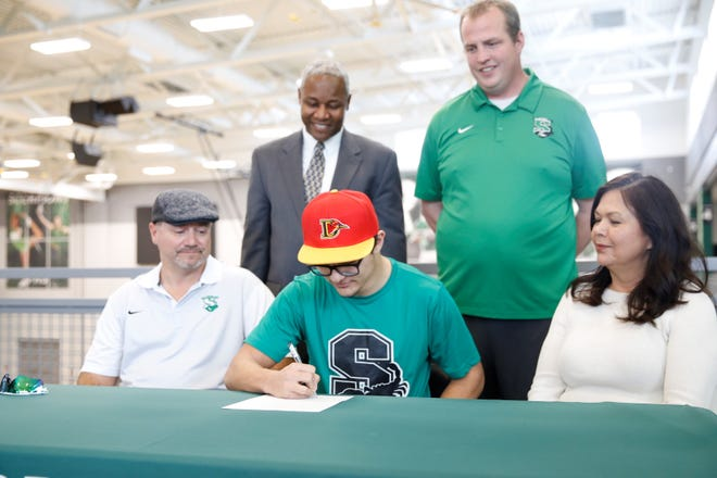 Farmington running back Johnny Shuttleworth signs his national letter of intent on Wednesday to continue his football career at College of the Desert in Palm Desert, California.