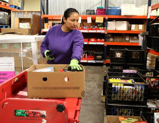 LaDonna Begay packs a food box, Wednesday, Jan. 9, 2019, for federal employees impacted by the government shutdown at ECHO Food Bank in Farmington.