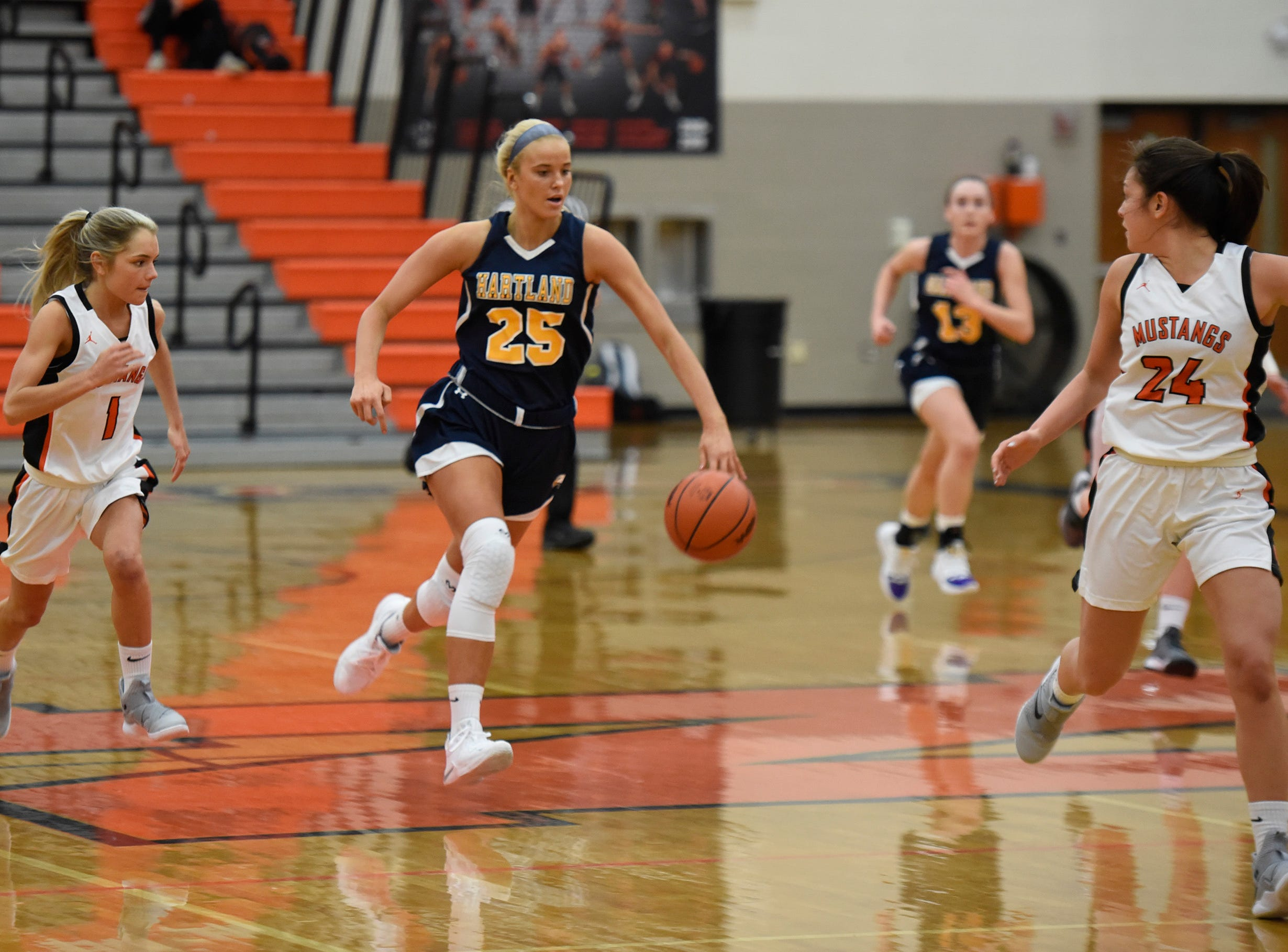 Hartland's Whitney Sollom (25) brings the ball up court with Northville's Jenna Lauderback (1) and Nicole Martin (24) during a KLAA match up between the Mustangs and Eagles at Northville Jan. 8, 2019