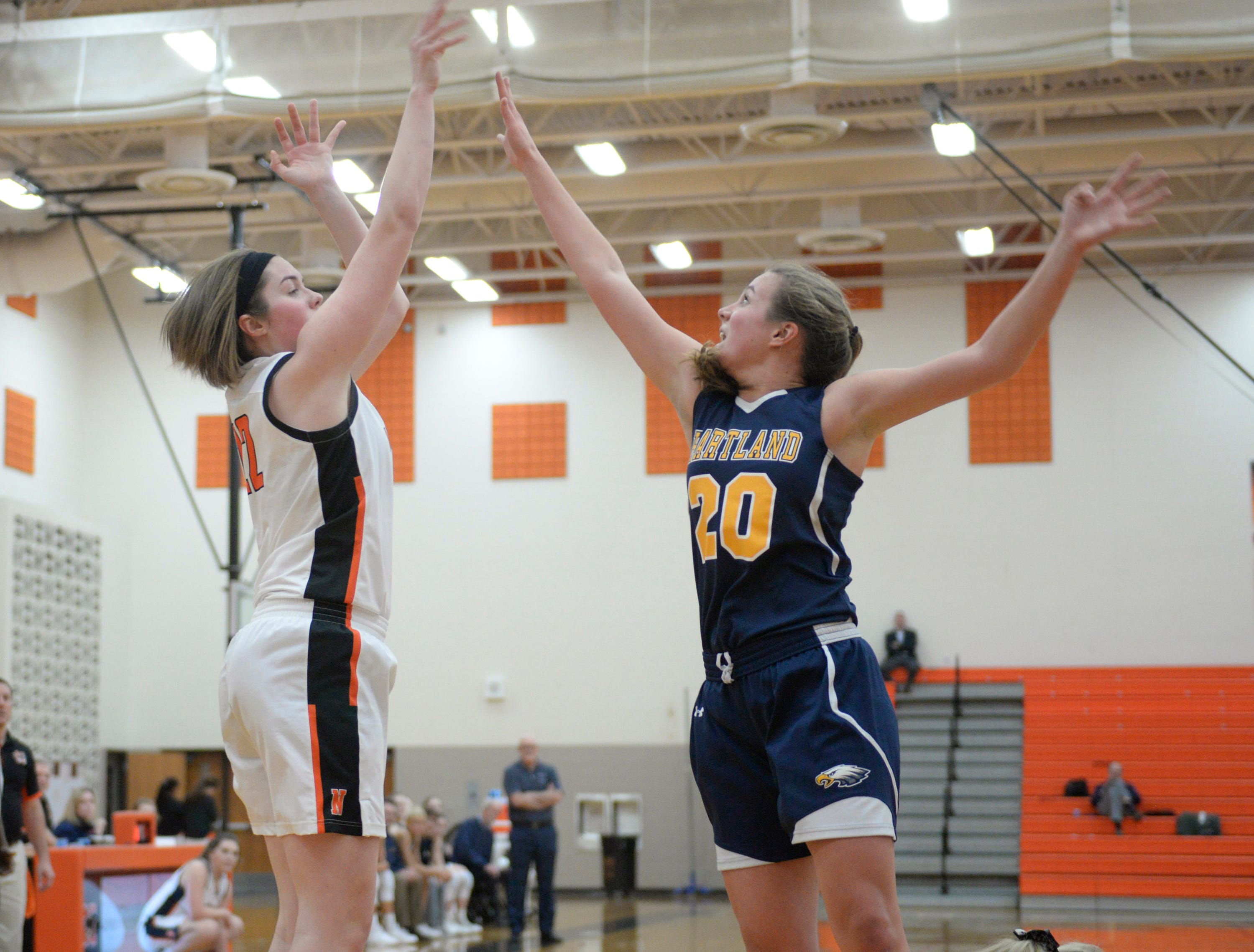 Northville's Sophia Jeromsky (21) gets a shot over Hartland's Lillee Gustafson (20) during a KLAA match up between the Mustangs and Eagles at Northville Jan. 8, 2019