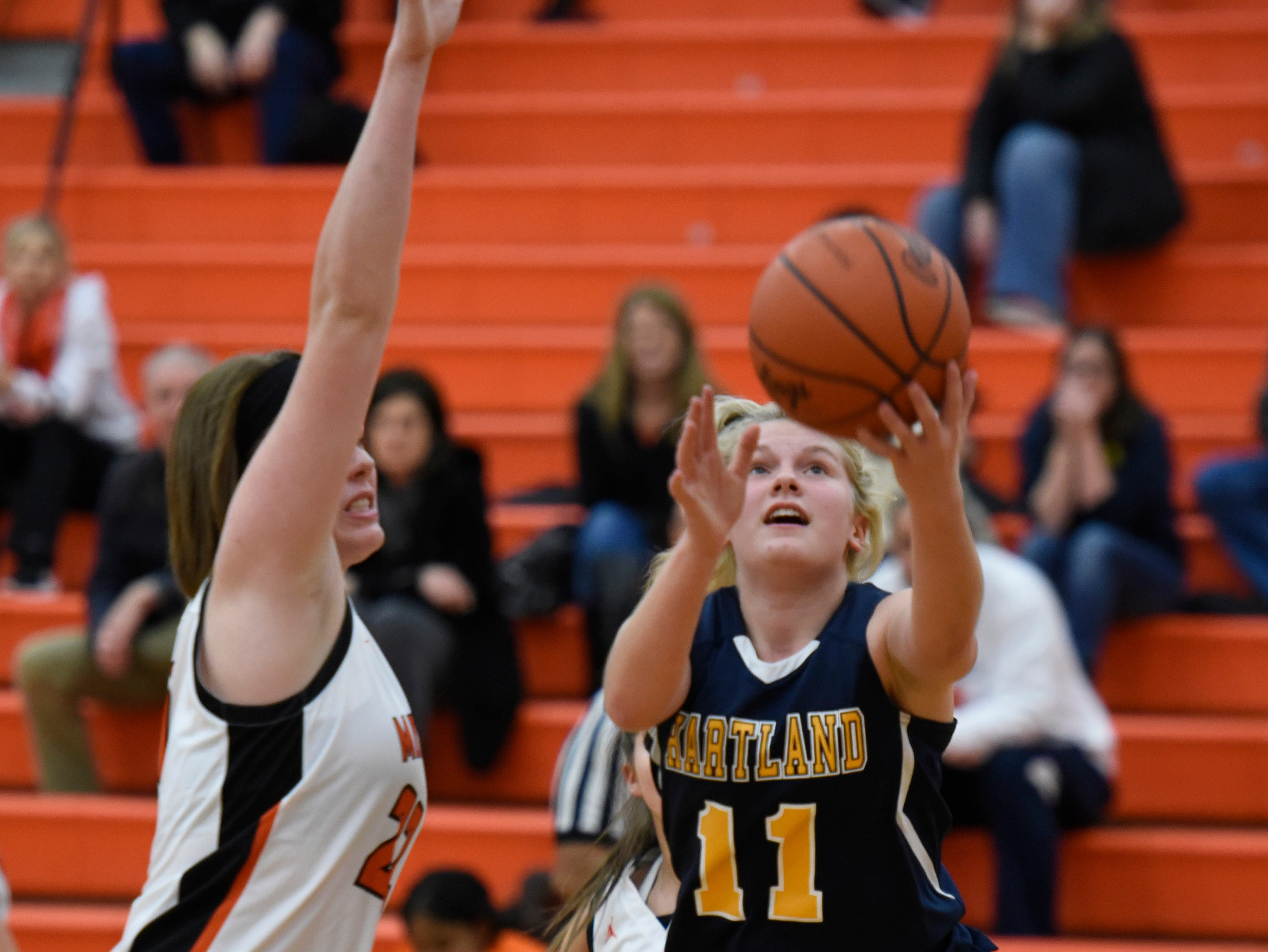 Hartland's Amanda Roach (11) drives by Northville's Nicole Martin (24) during a KLAA match up between the Mustangs and Eagles at Northville Jan. 8, 2019