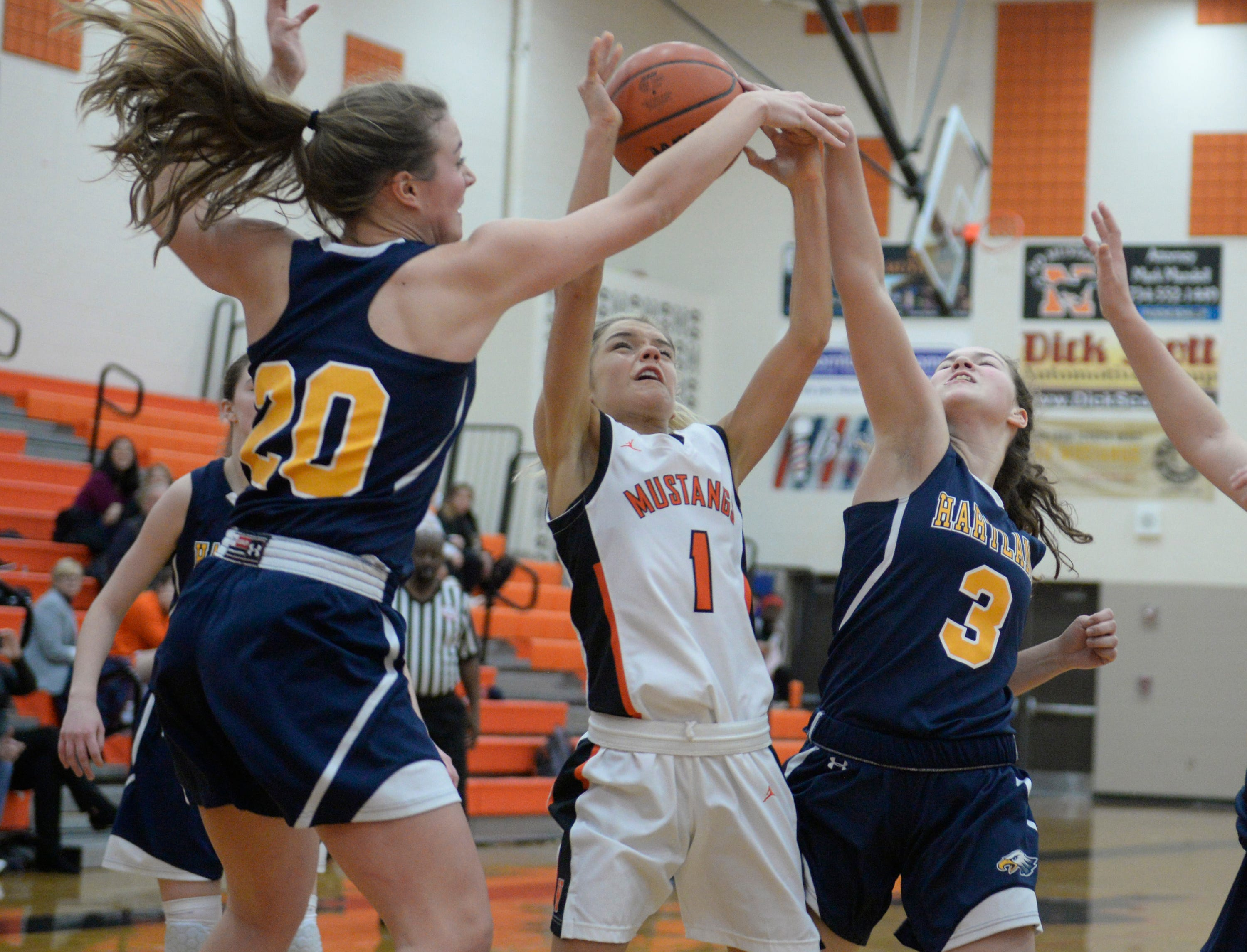 Northville's Jenna Lauderback (1) is guarded by Hartland's Lillee Gustafson (20) and Leah Lappin (3) during a KLAA match up between the Mustangs and Eagles at Northville Jan. 8, 2019