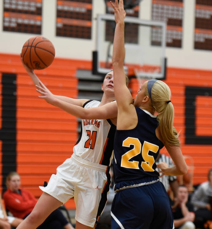 Northville's Sophia Jeromsky (21) and Hartland's Whitney Sollom (25) during a KLAA match up between the Mustangs and Eagles at Northville Jan. 8, 2019