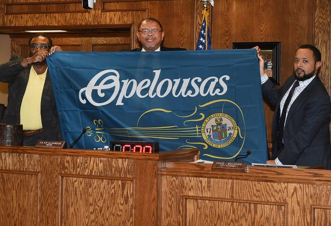 Mayor Julius Alsandor, center, and Alderman Floyd Ford, left, and City Attorney Travis Broussard display the Opelousas Tri-Centennial Flag presented to the city by Main Street Opelousas at Tuesday's city council meeting.