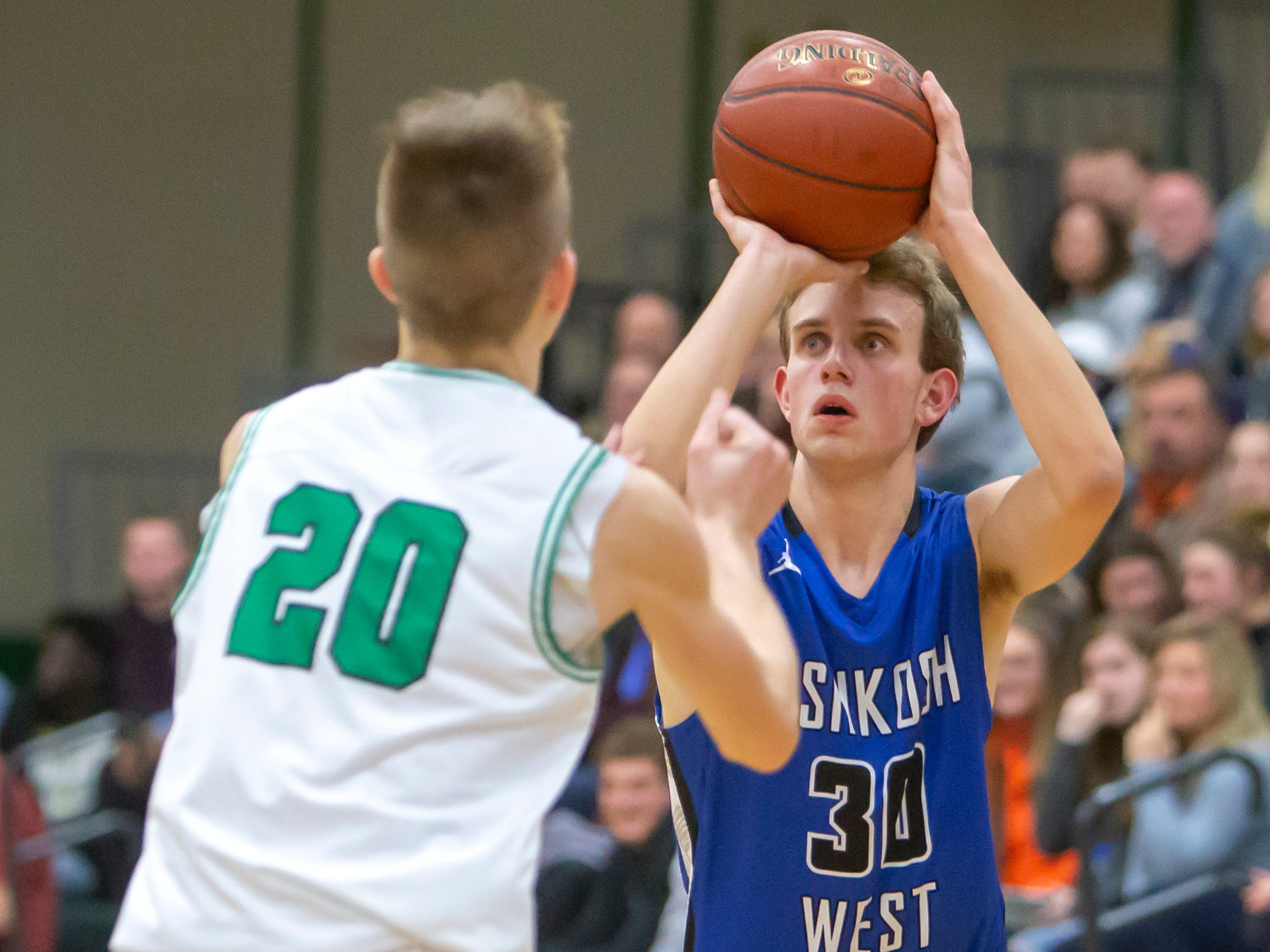 Oshkosh West's Caleb Fuller attempts a 3-pointer over Oshkosh North's Brennon Colburn at the Oshkosh North High School on Tuesday, Jan. 8, 2019.
