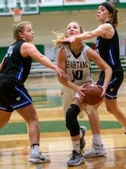 Oshkosh North's Brooke Ellestad drives between Oshkosh West's Lauren Olejnik and Anelise Hammonds on Tuesday at Oshkosh North High School.