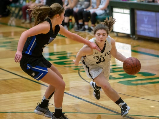 Oshkosh North's Meghan Gruse makes a drive around Laura Courchene at the Oshkosh North High School on Tuesday, January 8, 2019.