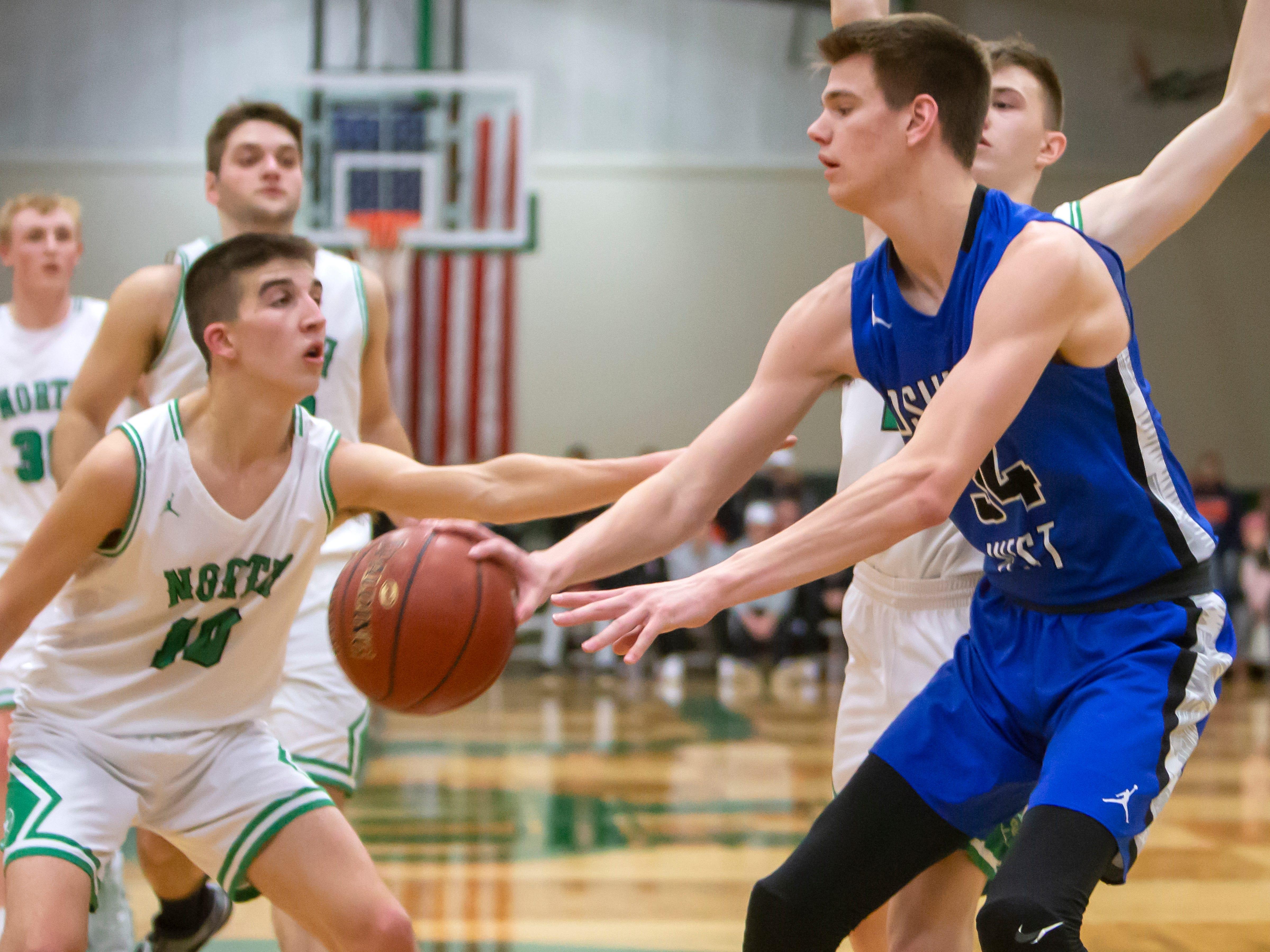 Oshkosh West's Luke Haasl passes the ball around Oshkosh North's Josh Dilling at the Oshkosh North High School on Tuesday, Jan. 8, 2019.