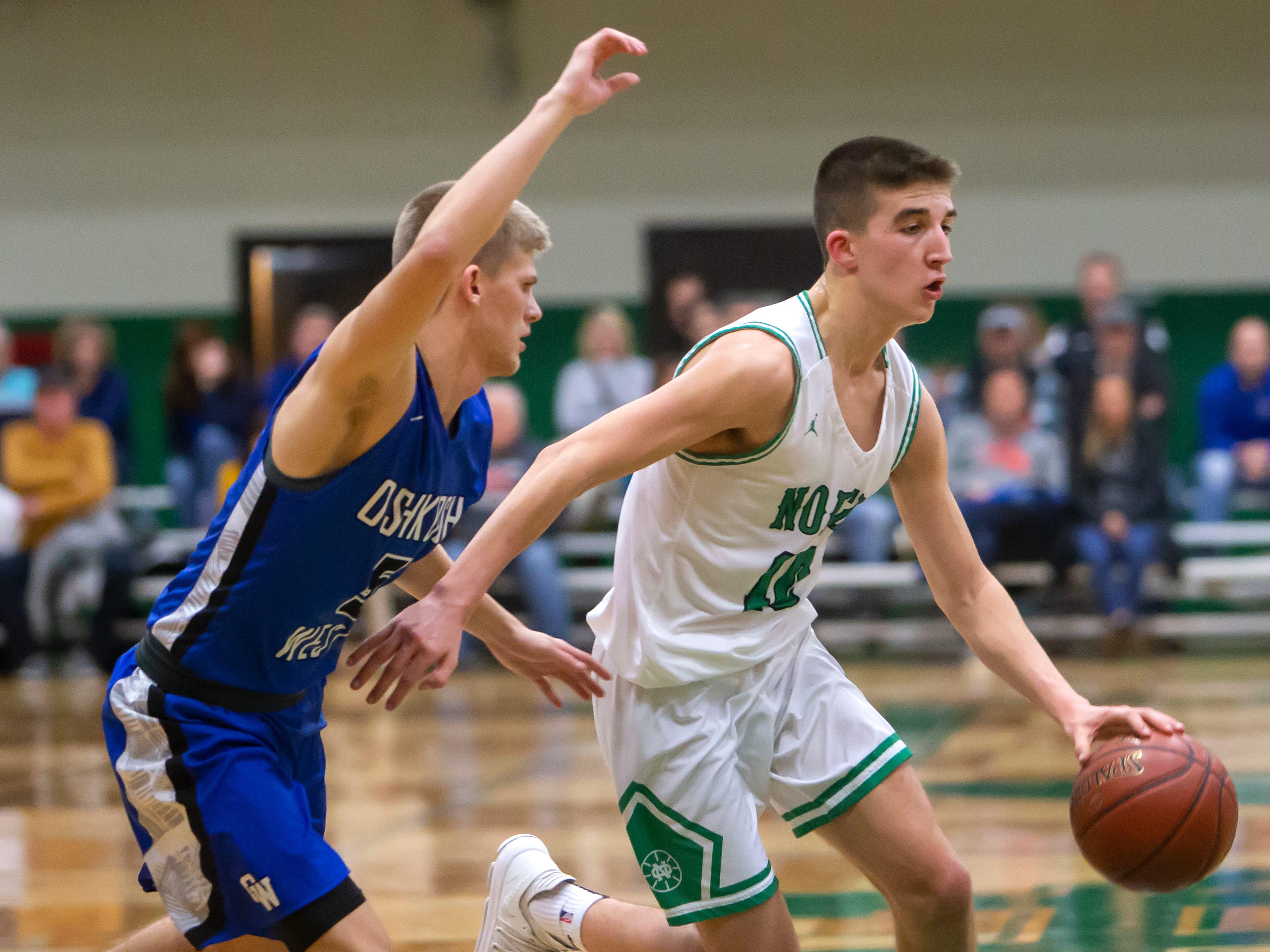 Oshkosh North's Josh Dilling drives the ball around Oshkosh West's AJ Ambroso at the Oshkosh North High School on Tuesday, Jan. 8, 2019.