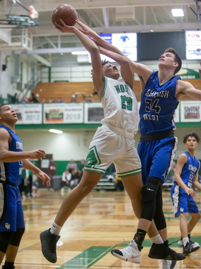 Oshkosh West's Luke Haasl goes up for the block against the shot by Oshkosh North's Jalen Keago at the Oshkosh North High School on Tuesday, Jan. 8, 2019.