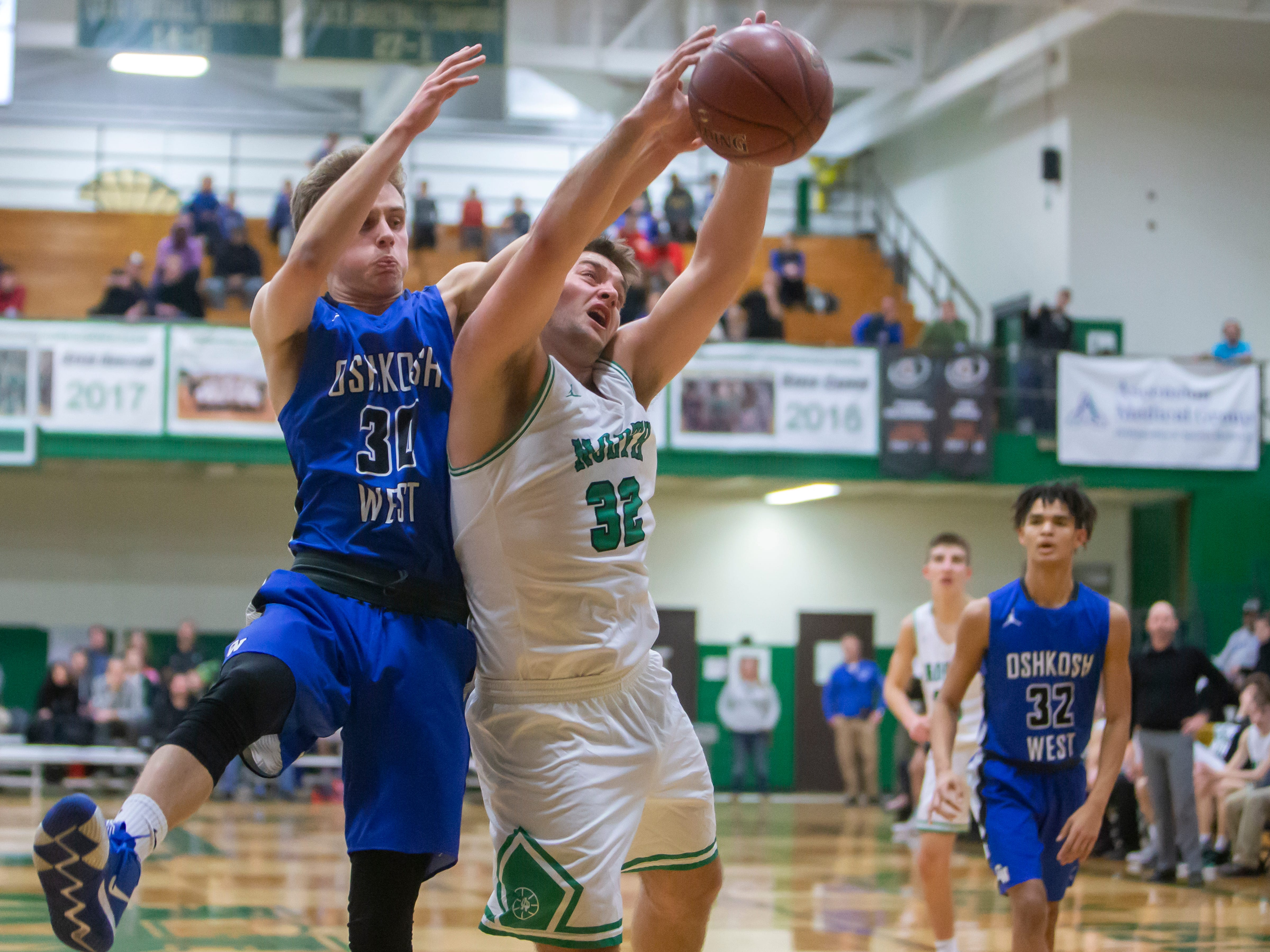 Oshkosh North's Matt Hickey attempts to gain control of the rebound in front of Oshkosh West's Caleb Fuller at the Oshkosh North High School on Tuesday, Jan. 8, 2019.