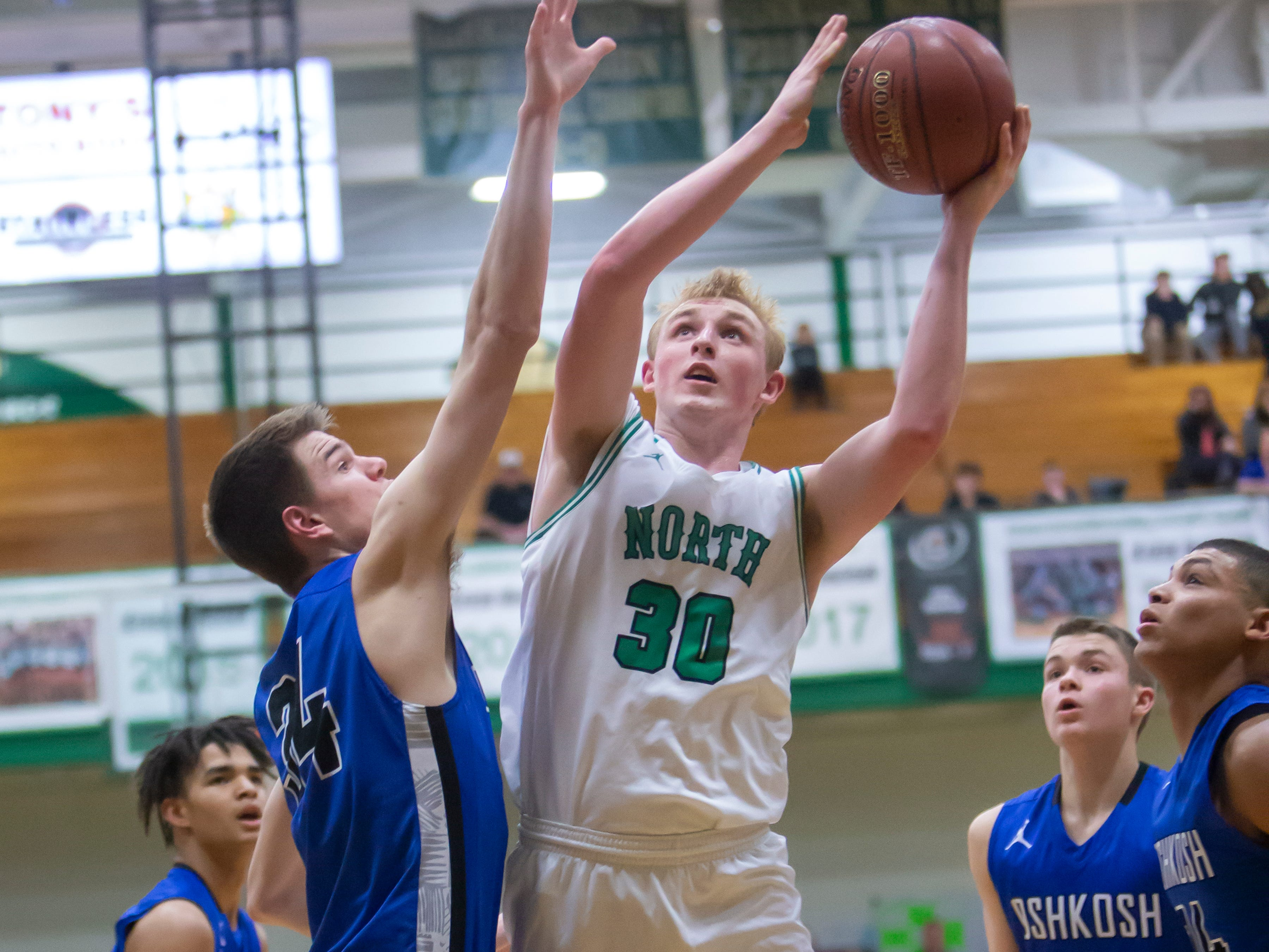 Oshkosh North's Matthew Berger goes up for a shot with Oshkosh West's Luke Haasl attempting to block the shot at the Oshkosh North High School on Tuesday, Jan. 8, 2019.