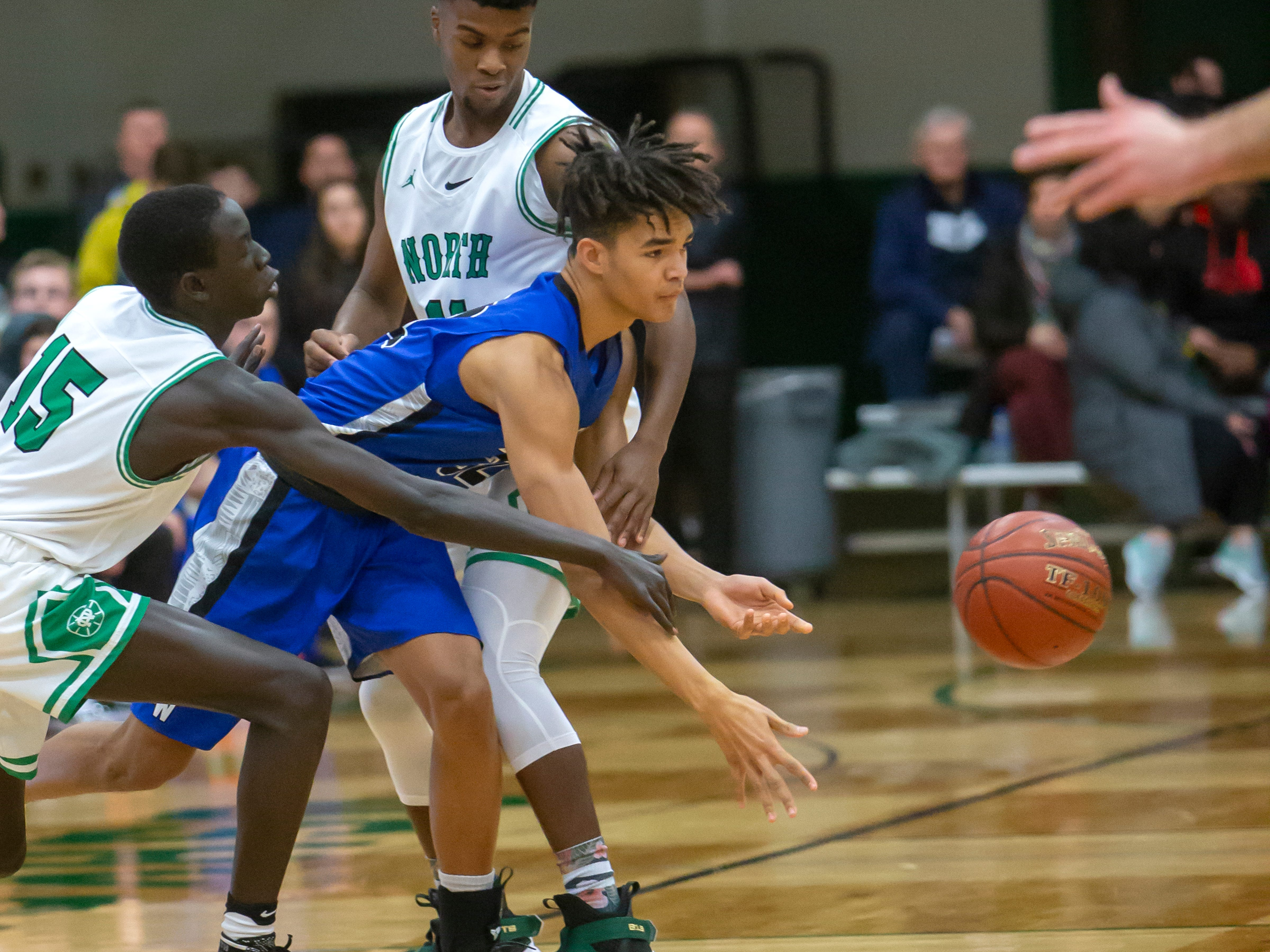 Oshkosh North's Garang Deng and Abe Schiek hold back Oshkosh West's Jacquez Overstreet going after the ball at the Oshkosh North High School on Tuesday, Jan. 8, 2019.