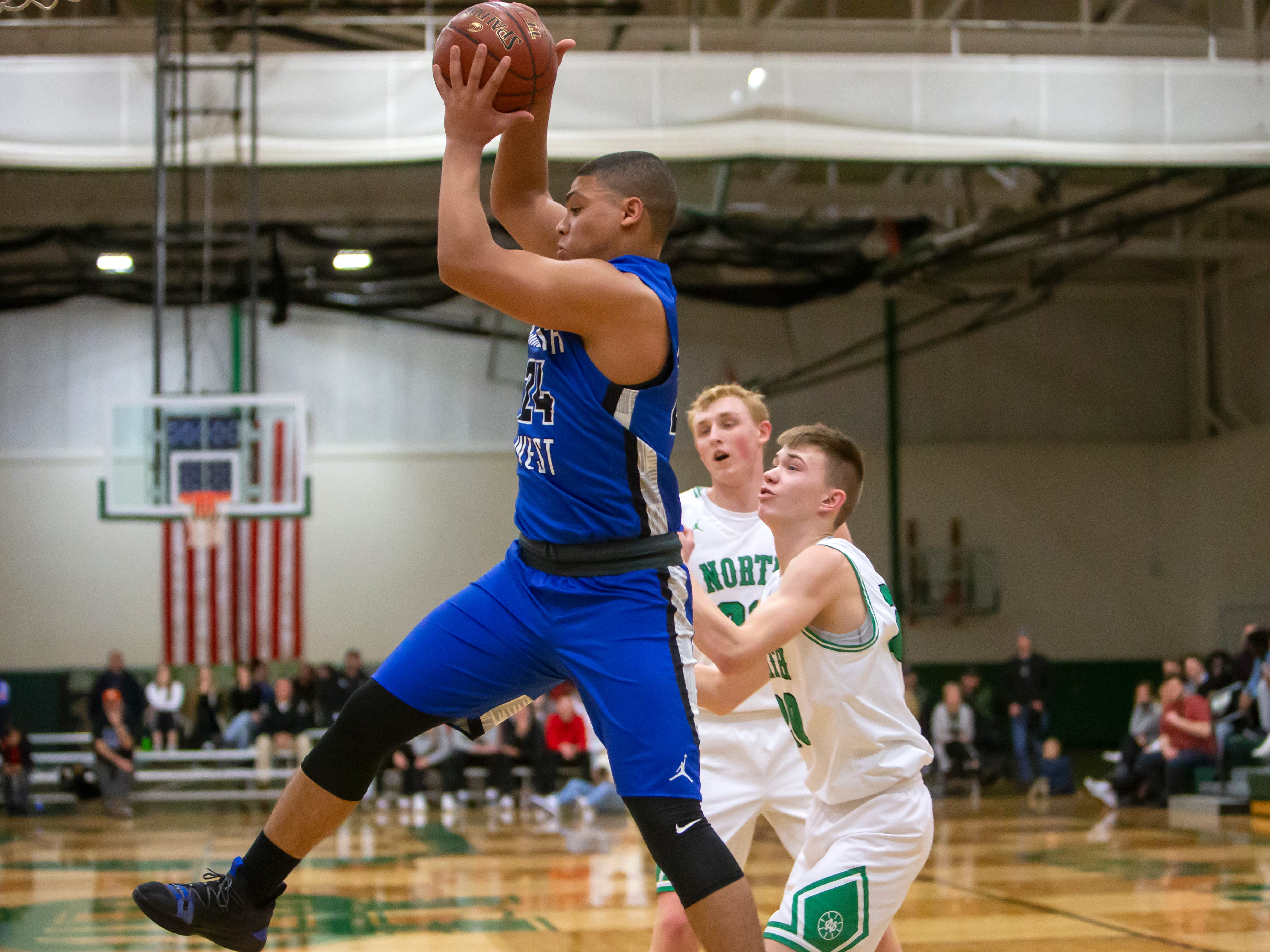 Oshkosh West's Karter Thomas comes down with the rebound playing against the Spartans at the Oshkosh North High School on Tuesday, Jan. 8, 2019.