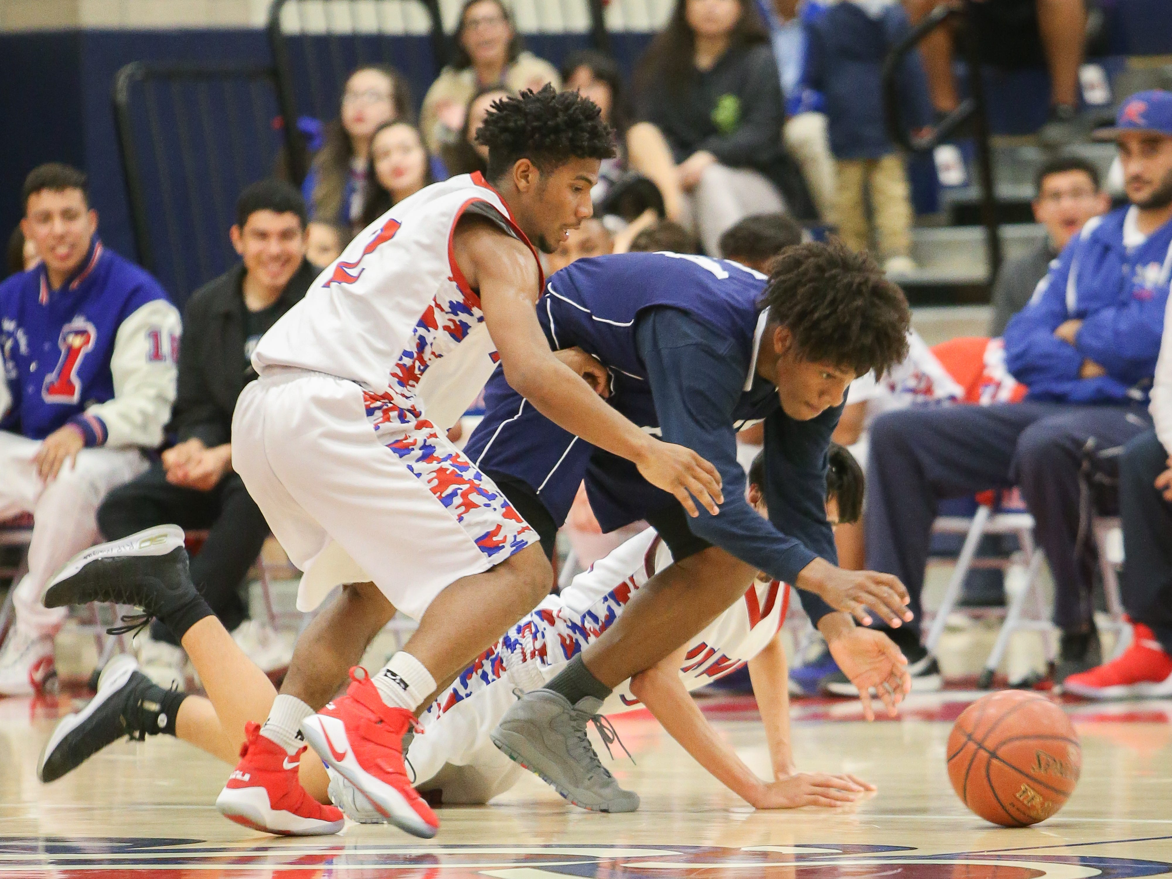 Players from both teams scrambles for the ball. The Indio varsity basketball team won Tuesday's home conference game against Desert Hot Springs (CA) by a score of 64-59.