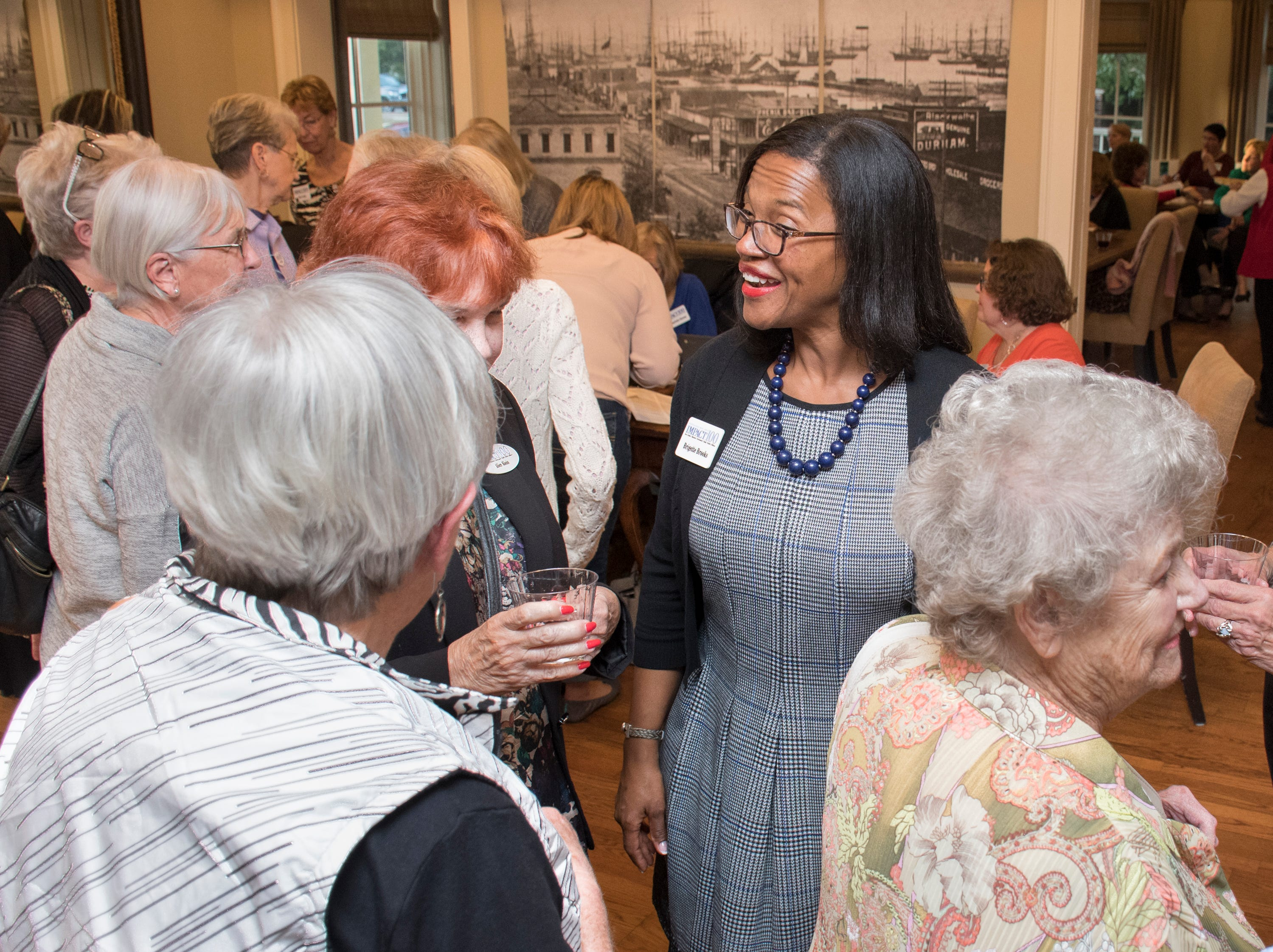 President Brigette Brooks chats with other members during the Impact 100 Pensacola Bay Area meeting at the Lee House in Pensacola on Tuesday, January 8, 2019.