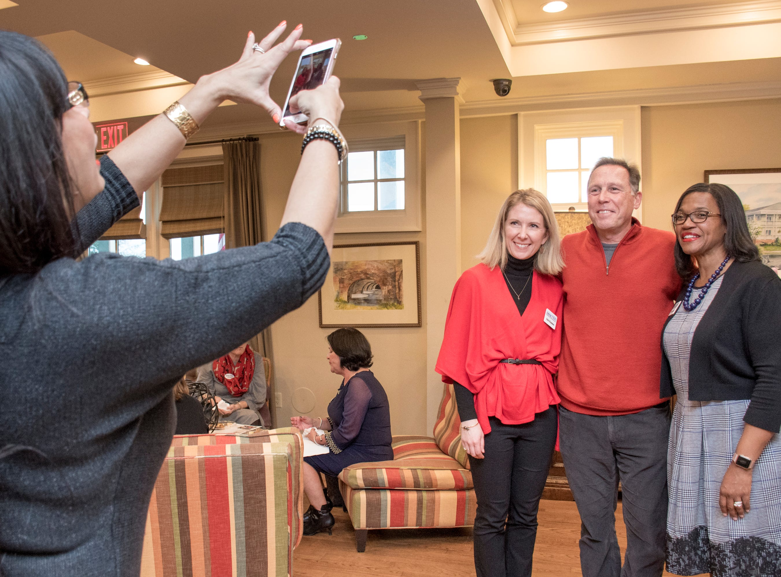Madrina Ciano snaps a photo of Katie Kingsman, guest speaker Andy Caputi, Vice President of the Veterans Memorial Park, and president Brigette Brooks during the Impact 100 Pensacola Bay Area meeting at the Lee House in Pensacola on Tuesday, January 8, 2019.