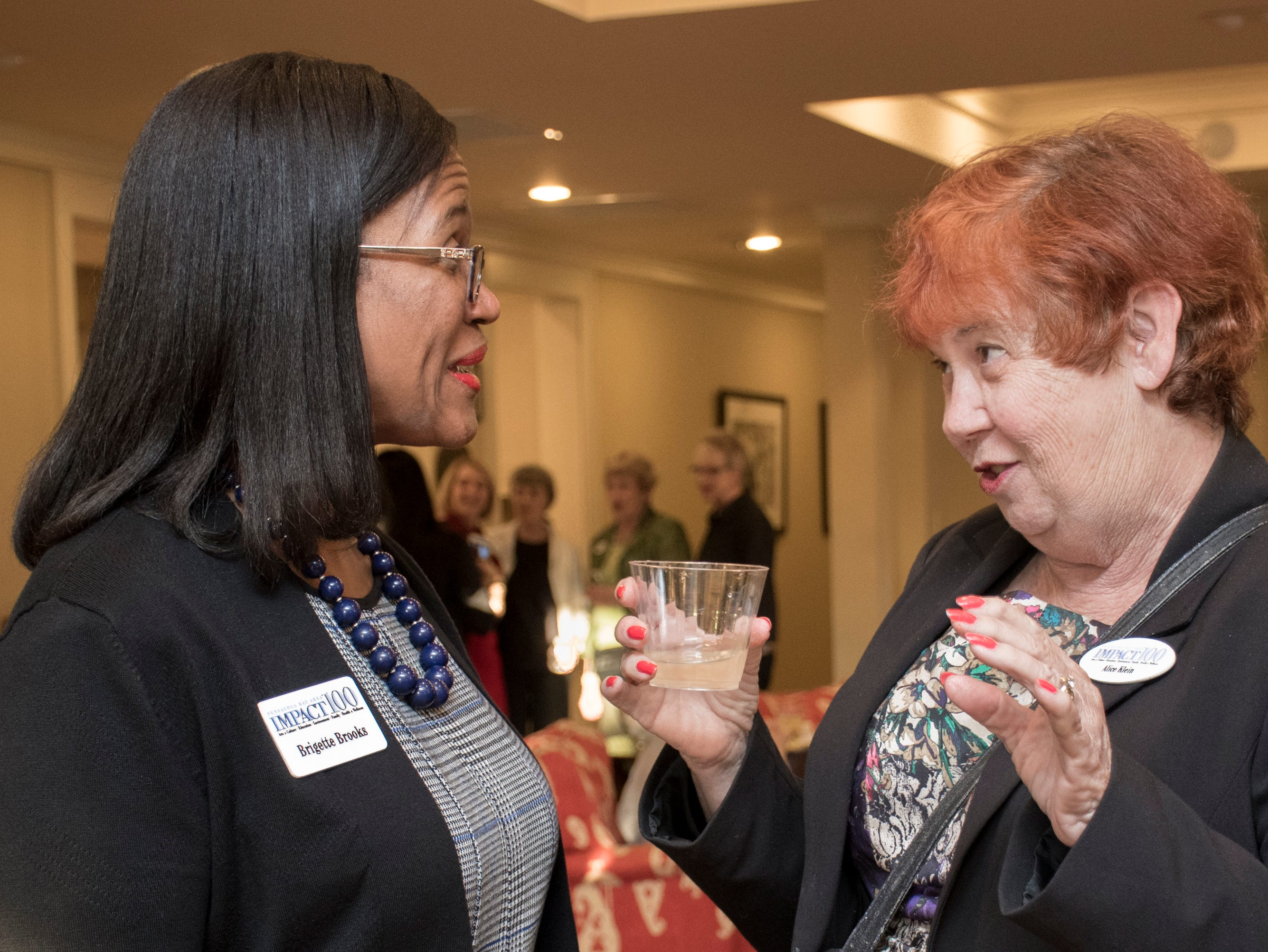President Brigette Brooks, left, and Alice Klein chat during the Impact 100 Pensacola Bay Area meeting at the Lee House in Pensacola on Tuesday, January 8, 2019.