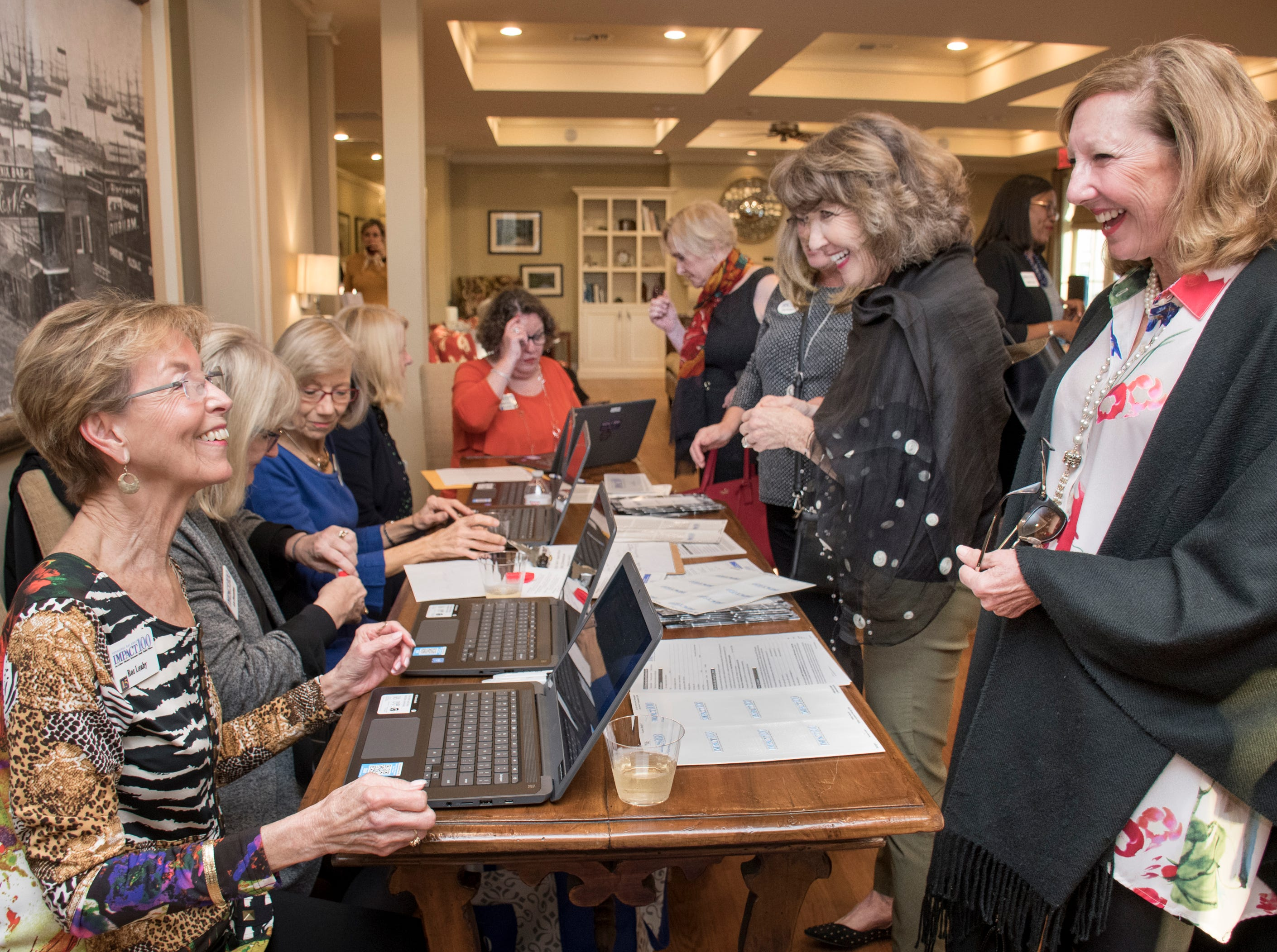 Roz Leahy, left, checks in Suzanne Manziek during the Impact 100 Pensacola Bay Area meeting at the Lee House in Pensacola on Tuesday, January 8, 2019.