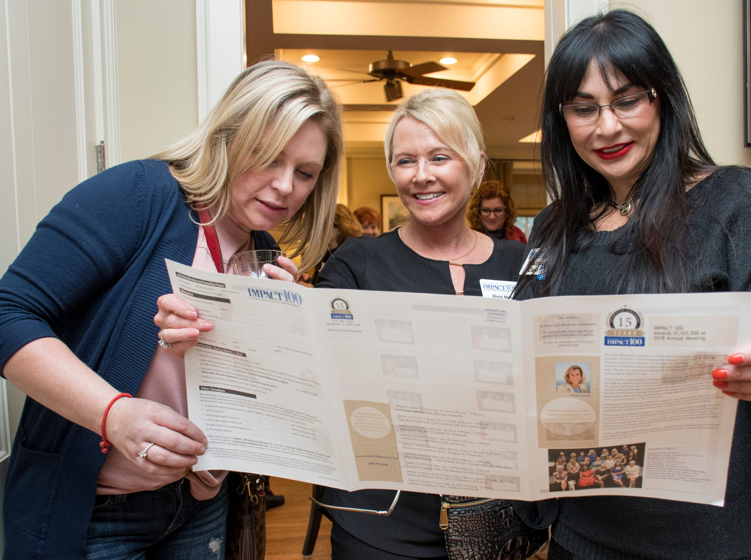 Kellie Hardy, from left, Alicia Ahern, and Madrina Ciano look over a newsletter during the Impact 100 Pensacola Bay Area meeting at the Lee House in Pensacola on Tuesday, January 8, 2019.