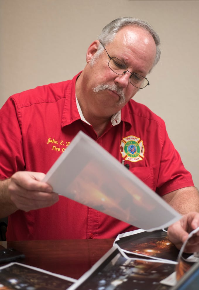 """Fire Chief John Reble looks through photos of the """"2009 Caroline Street Fire"""" at the Milton Fire Station in Milton on Tuesday, January 8, 2019."""