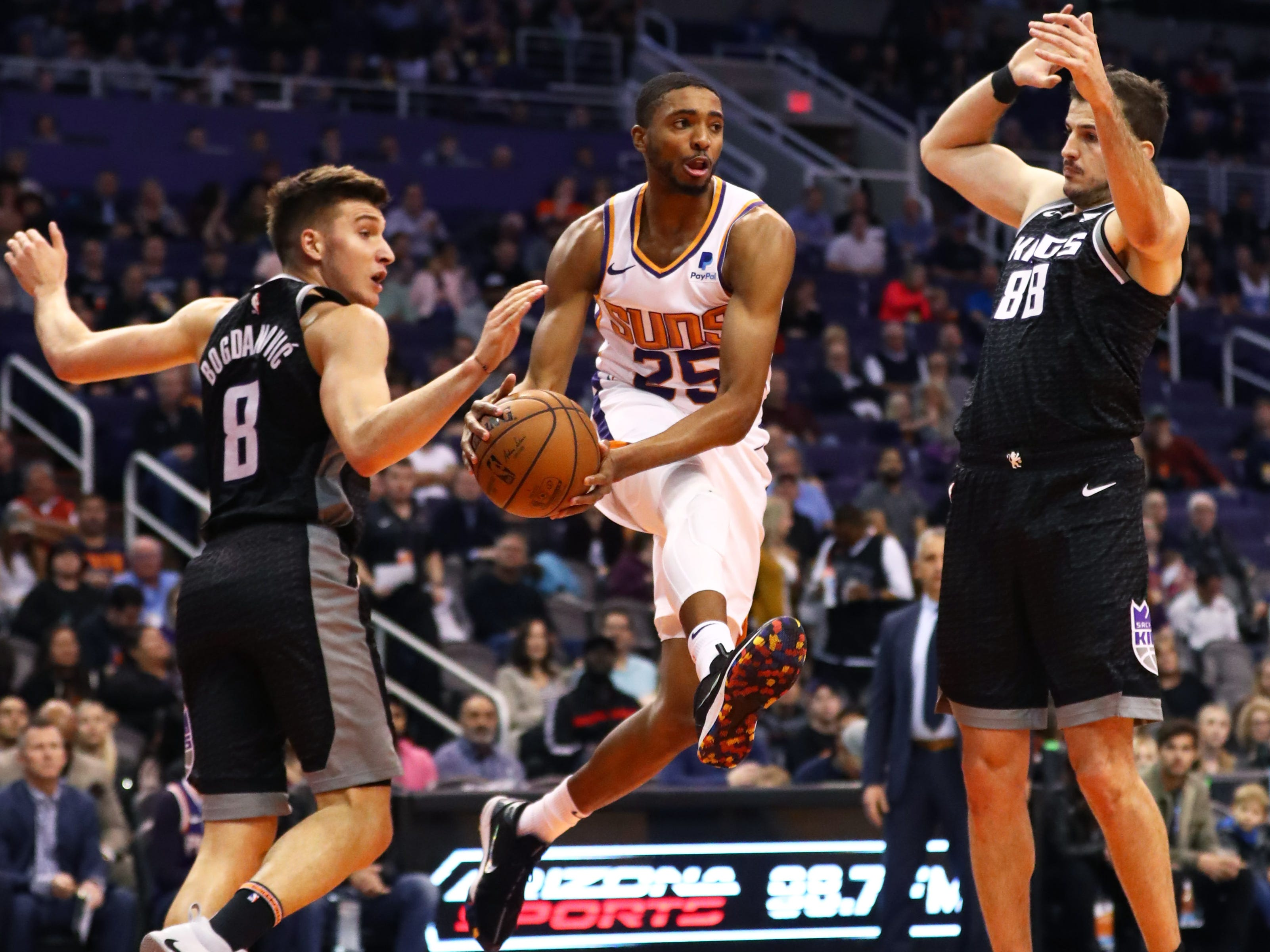 Jan 8, 2019; Phoenix, AZ, USA; Phoenix Suns forward Mikal Bridges (25) passes the ball against Sacramento Kings guard Bogdan Bogdanovic (8) and forward Nemanja Bjelica (88) in the first half at Talking Stick Resort Arena. Mandatory Credit: Mark J. Rebilas-USA TODAY Sports